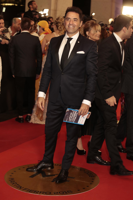 """Mariano Iúdica, ganador por """"Polémica en el Bar"""" con un clásico black tie de solapas de raso con corbata negra, camisa blanca con gemelos y zapatos abotinados de cuero negro."""