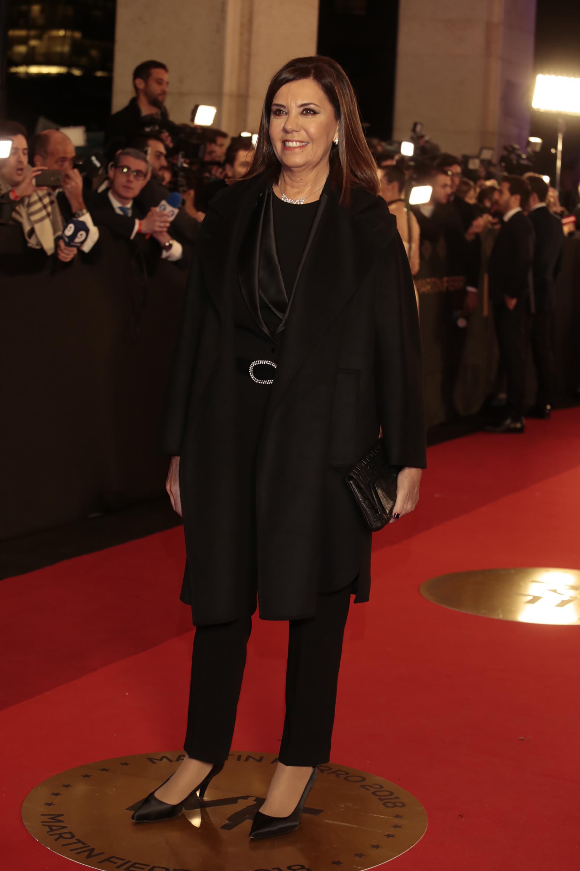 Liliana Parodi eligió un smoking femenino en total black. Lo combinó con tapado, stilettos de raso en punta y clutch de cuero.