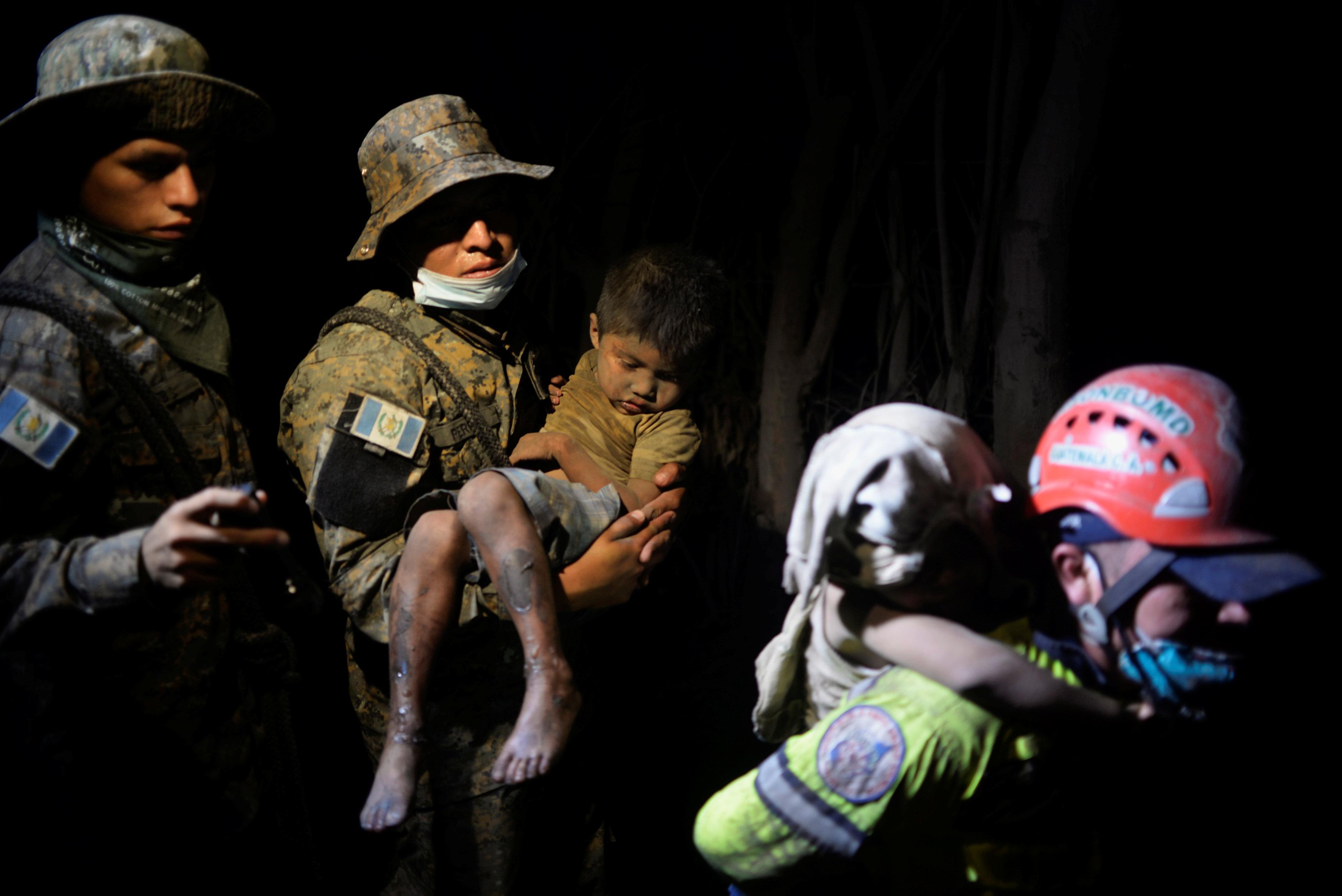 Un niño cubierto de cenizas es rescatado en EL Rodeo (REUTERS/Fabricio Alonzo)