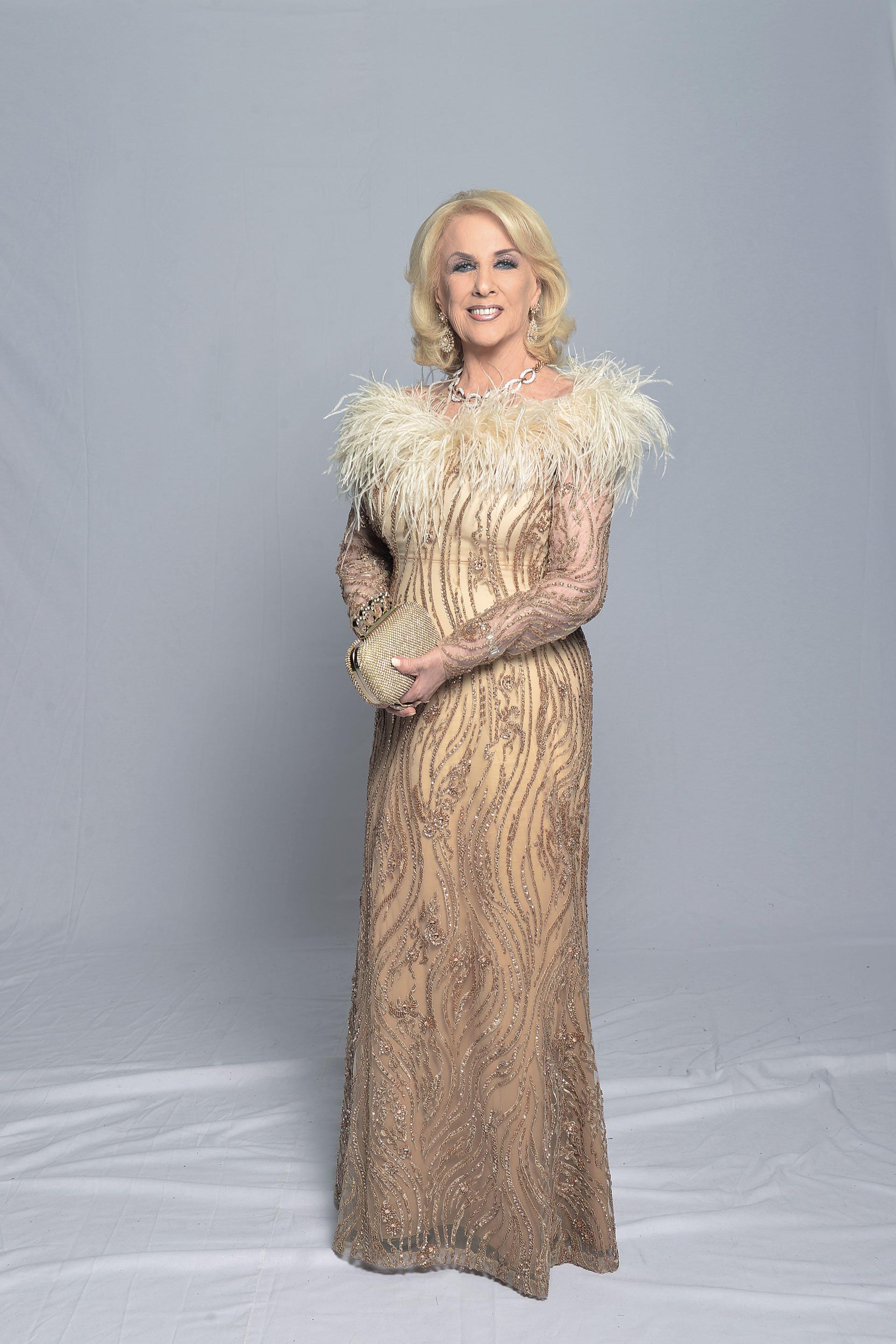Mirtha en vestido bordado y plumas en escote by Iara, clutch Dior y joyas personales.