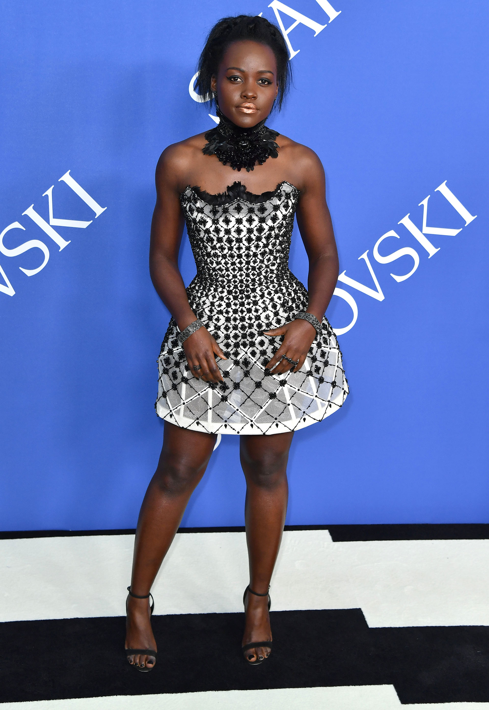 Lupita Nyong'o, con un minivestido encorsetado en blanco y negro e incrustaciones de cristales de Swarovski y collar al tono. Todo, de Atelier Versace
