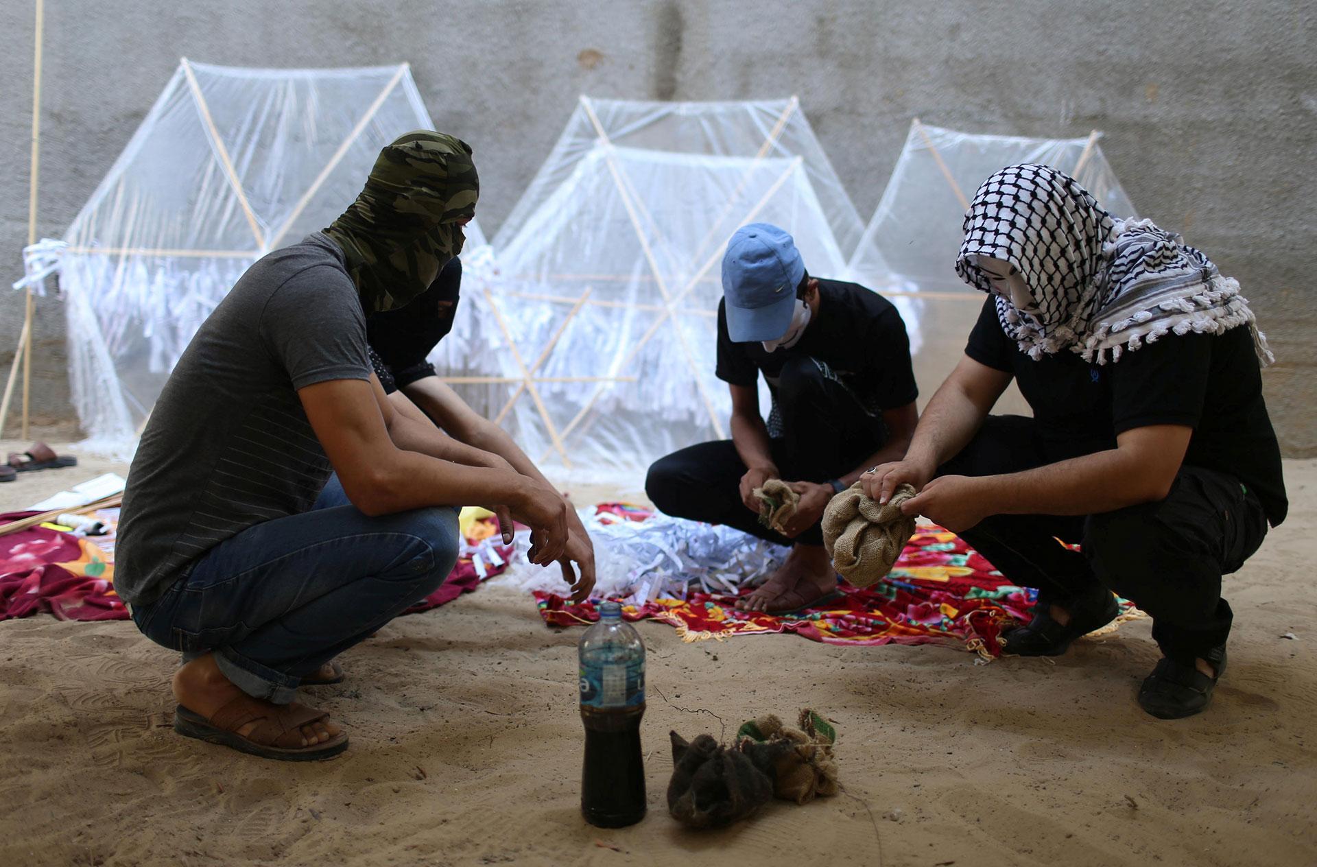 Tres palestinos empapan los trapos con combustible para luego encenderlos al lanzar las cometas (Reuters)
