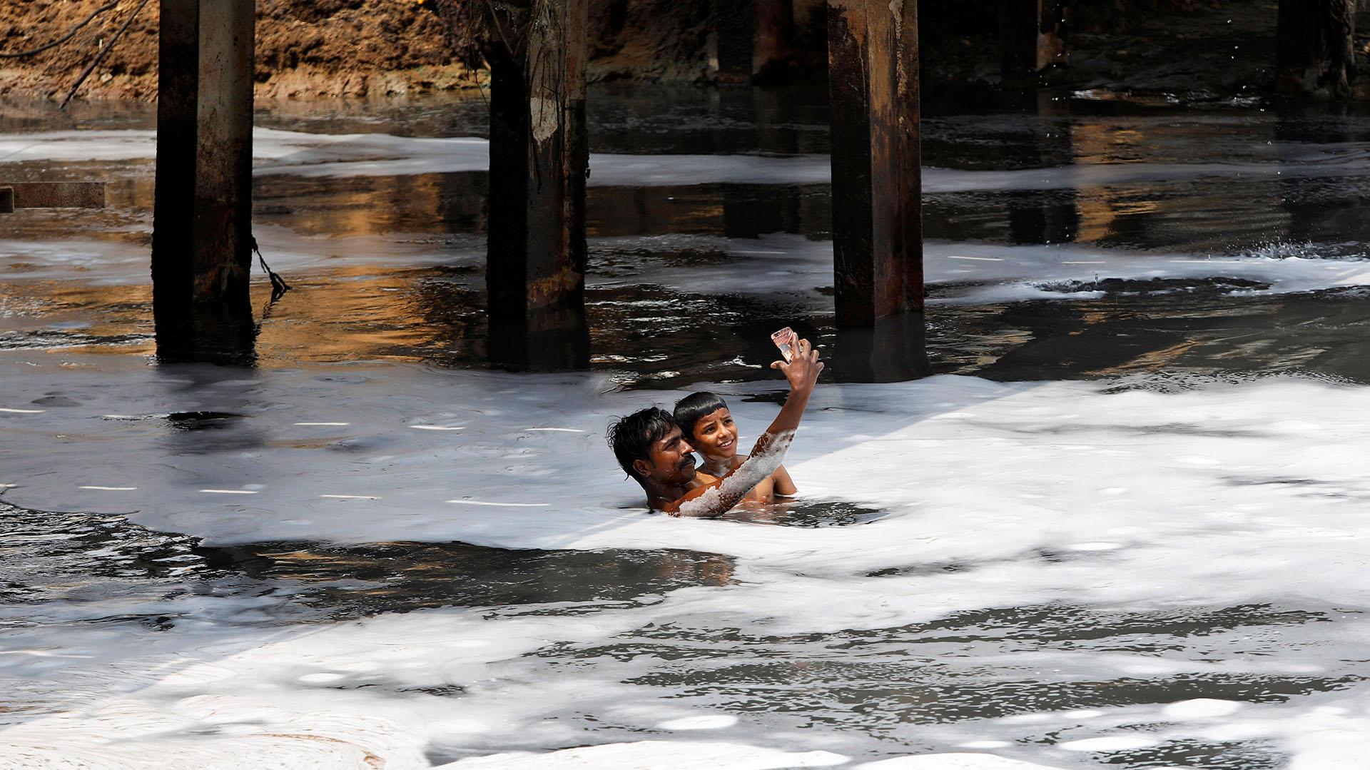Un hombre y un niño sonríen para unafoto mientras nadan en las contaminadas aguas del Río YamunaenNueva Delhi, India (REUTERS/Saumya Khandelwal)