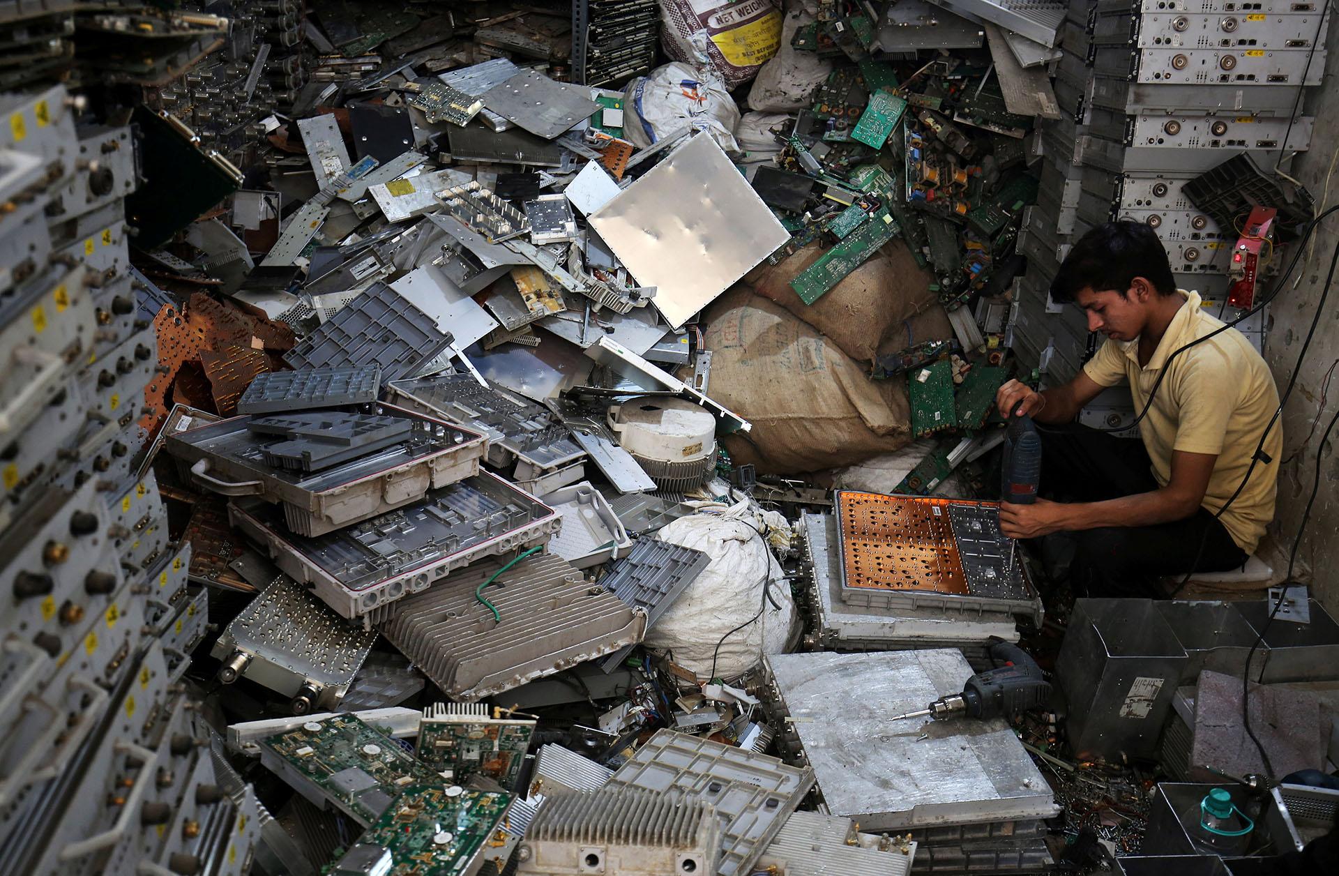 Un trabajador desarma basura electrónica en un taller en Nueva Delhi, India (REUTERS/Amit Dave)