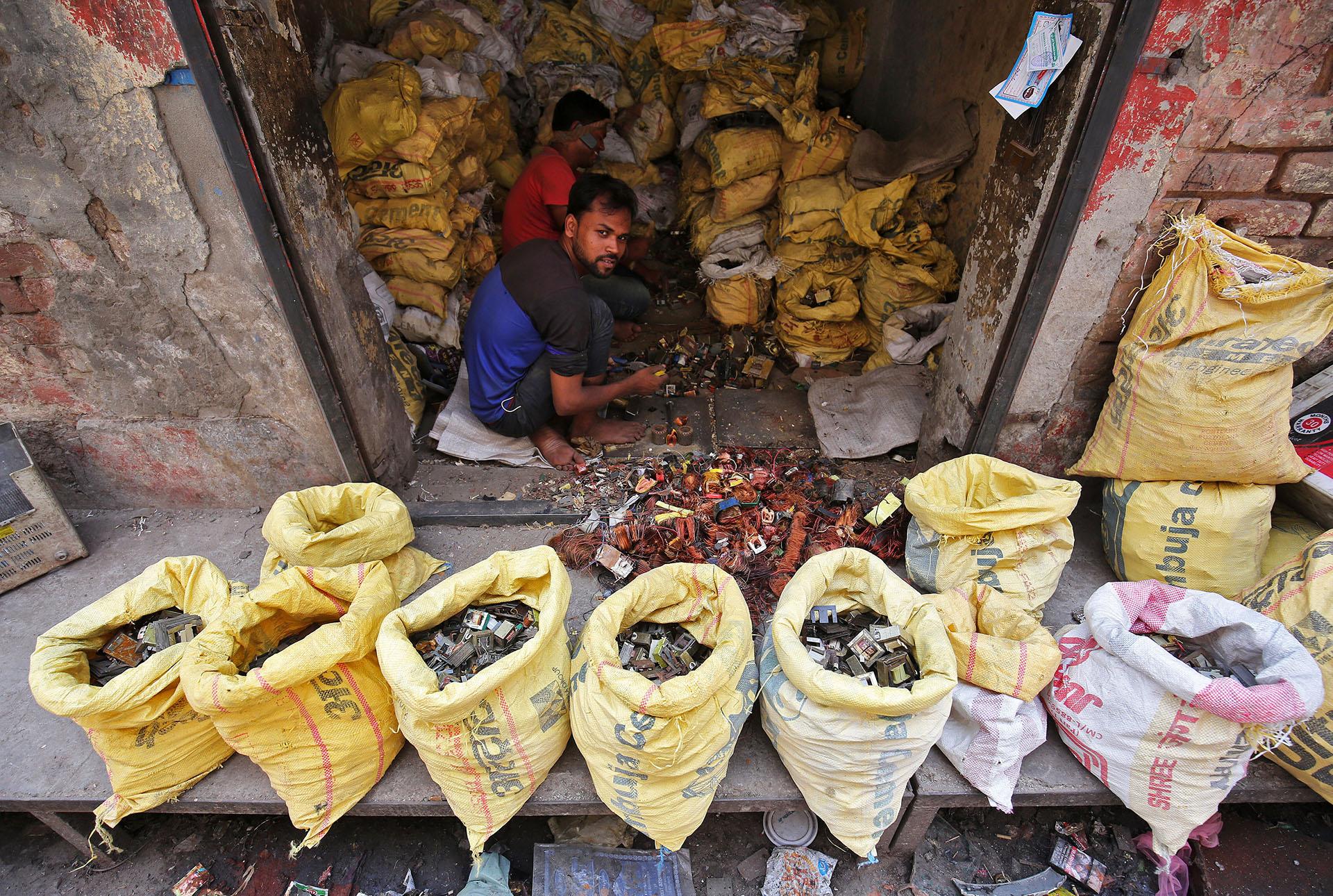 TRabajadores desarmando piezas de basura electrónica en un taller de Nueva Delhi, India (REUTERS/Amit Dave)