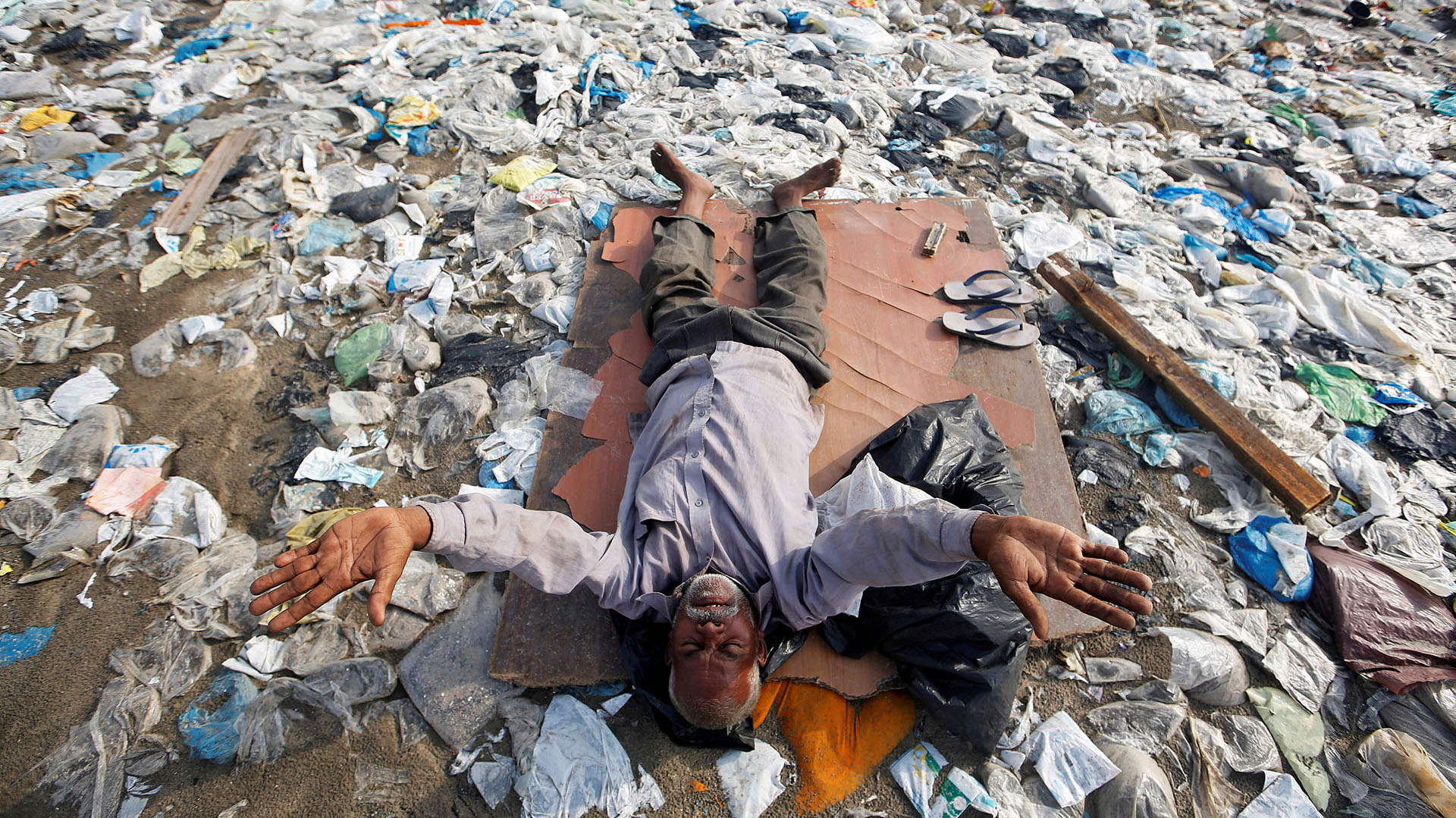 Un hombre se recuesta en una playa repleta de basura en Mumbai, India (REUTERS/Francis Mascarenhas TPX IMAGES OF THE DAY)