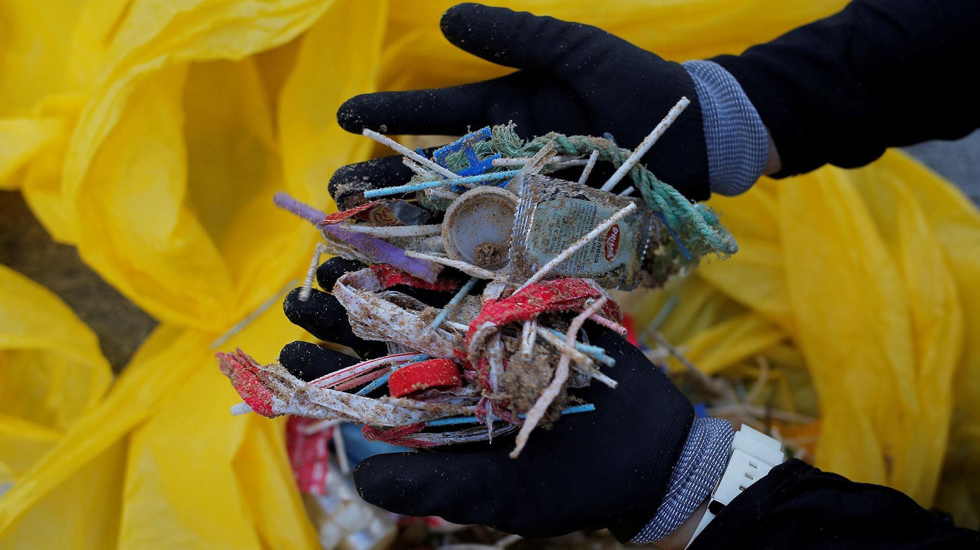 Un voluntario muestra hisopos y plásticos recogidos en la playa La Costilla, en Rota, España (REUTERS/Jon Nazca/File Photo)