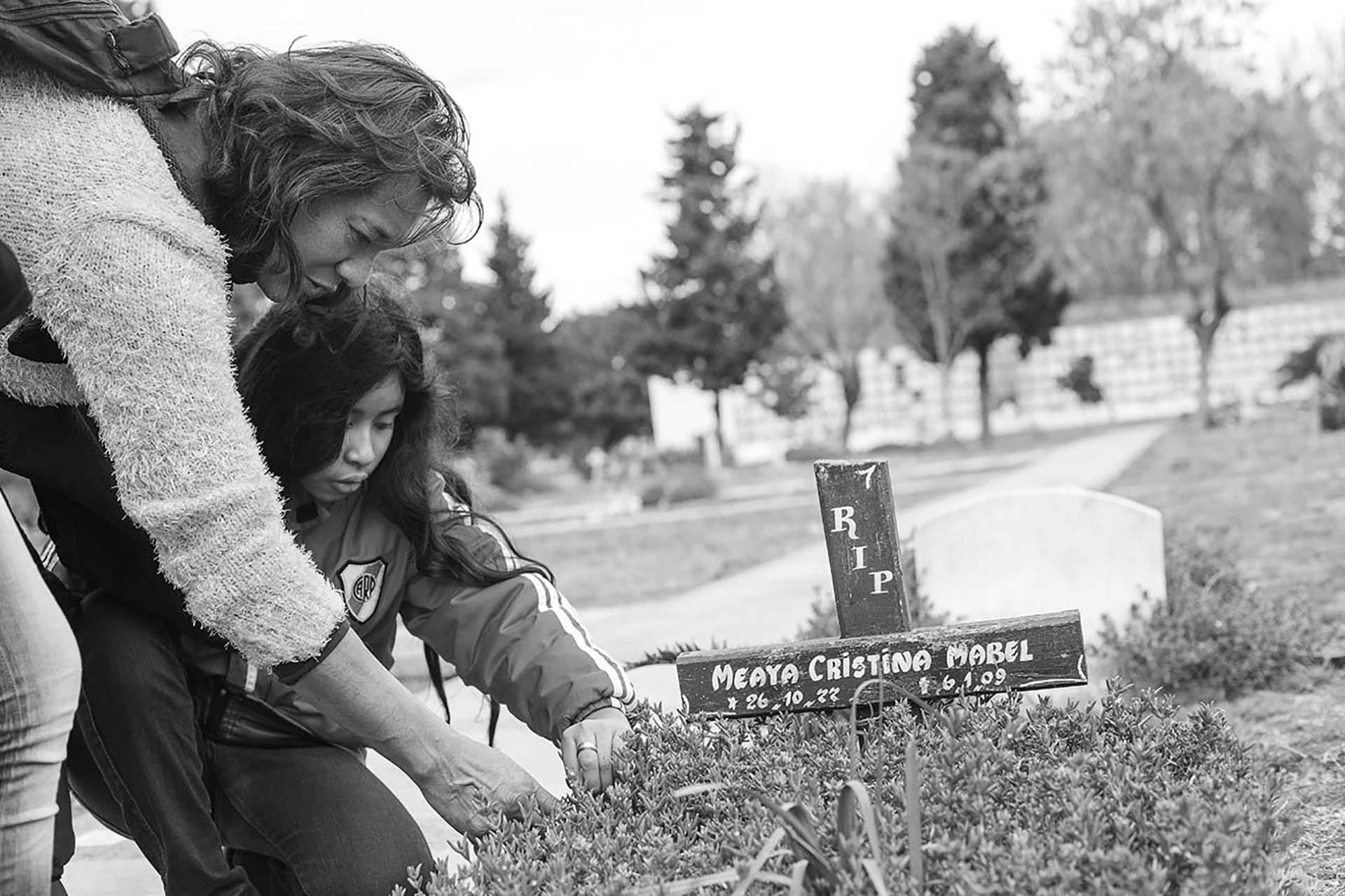 Cinthia y Zamira en el Cementerio de Chacarita, junto a la tumba de Cristina Mabel, quien fue su pareja y madre de las niñas