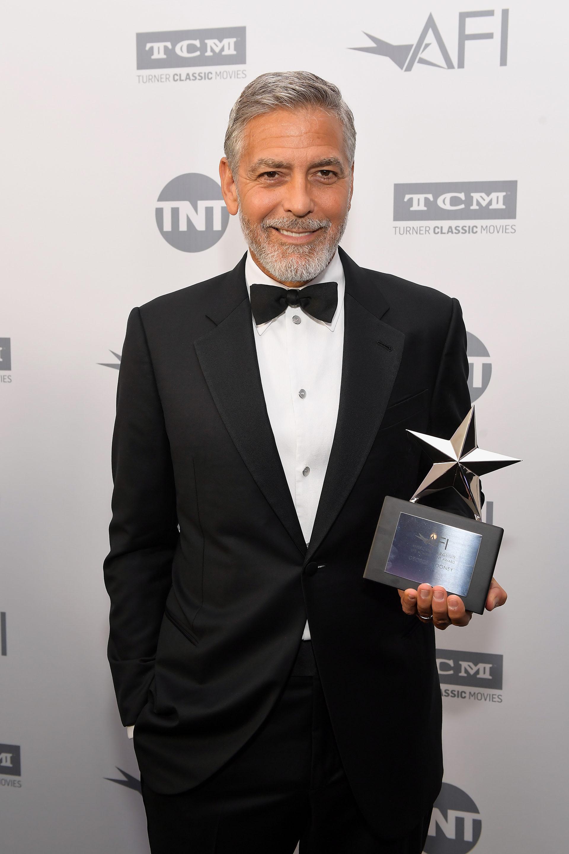 Vestido con un elegante smoking, George Clooney posa con su premio