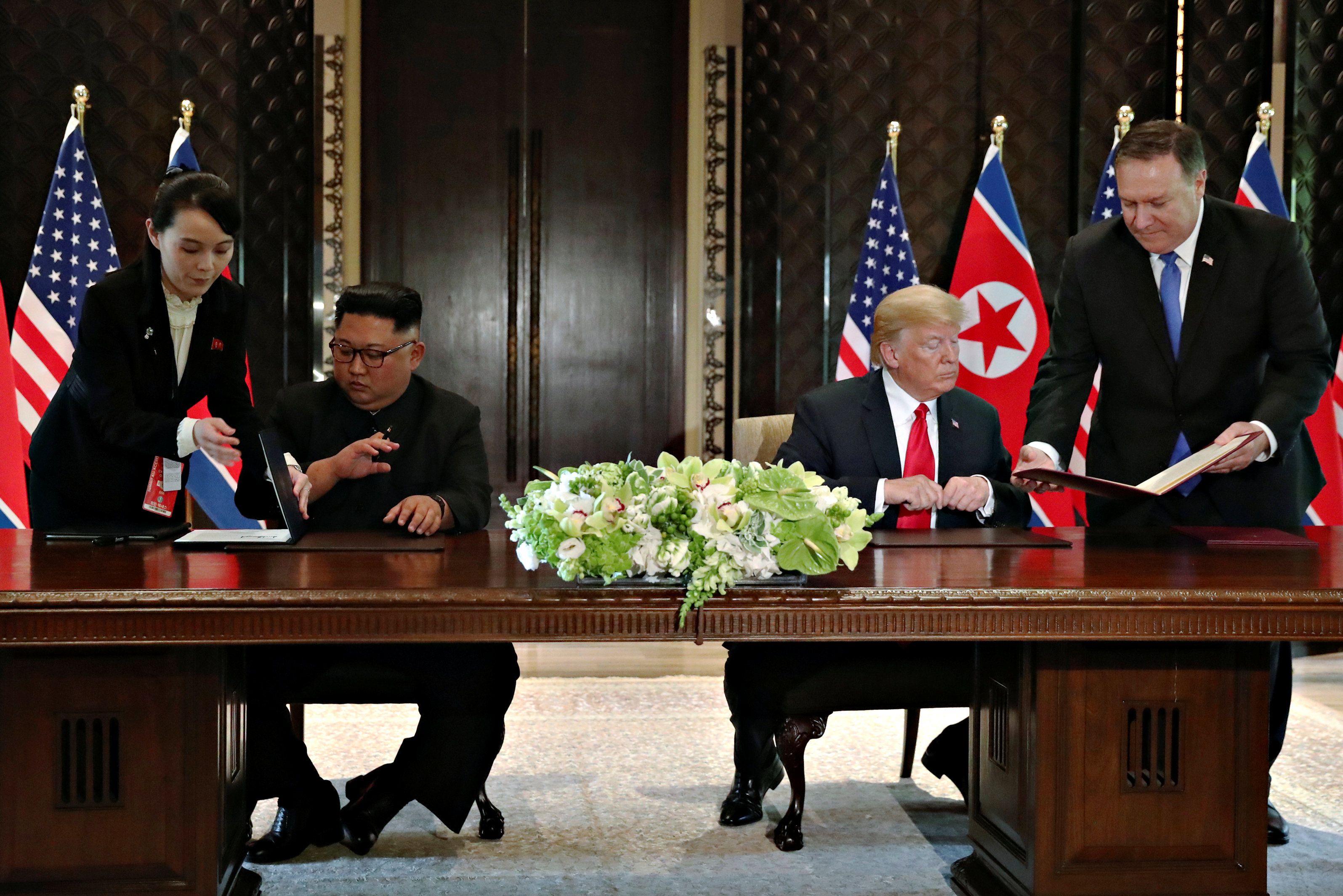 Kim Jong-un, acompañado de su hermana Kim Yo-jong, firma al declaración de Singapur junto a Donald Trump, acompañado por el Secretario de Estado Mike Pompeo(Reuters)