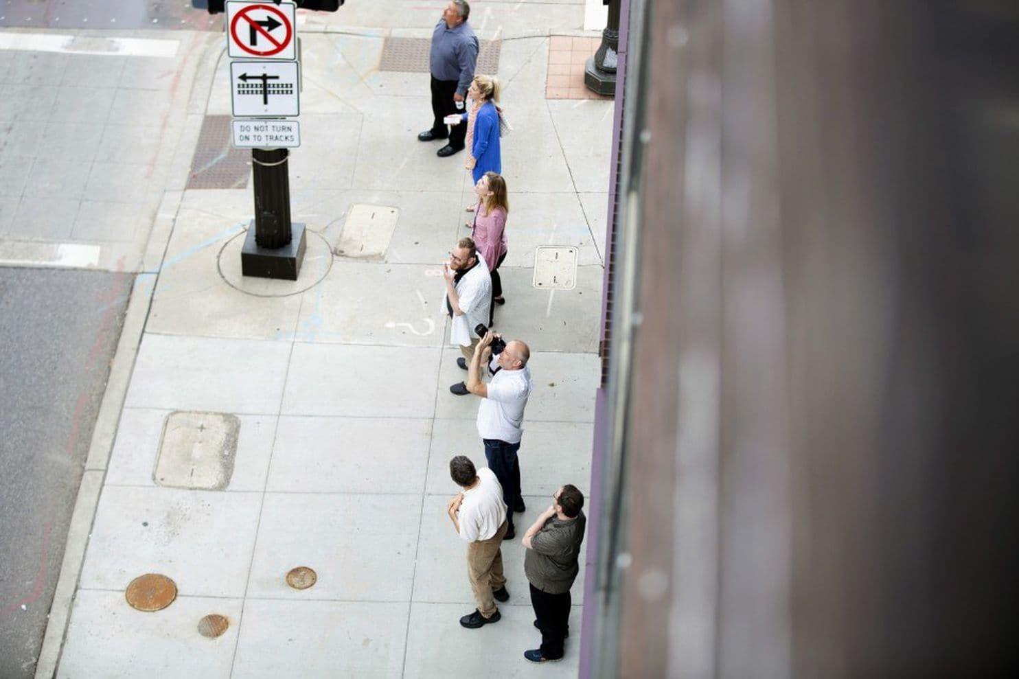 Los peatones se detenían en la calle 7de St. Paulpara mirar al mapache que escala la Torre UBS. (Evan Frost/Minnesota Public Radio/AP)