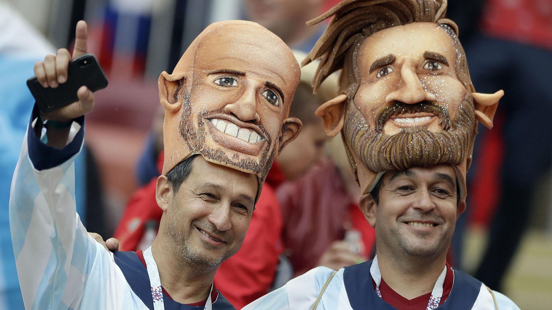 Dos hinchas argentinos en la ceremonia de inauguración del Mundial lucen las caretas de Mascherano y Messi(AP Photo/Matthias Schrader)