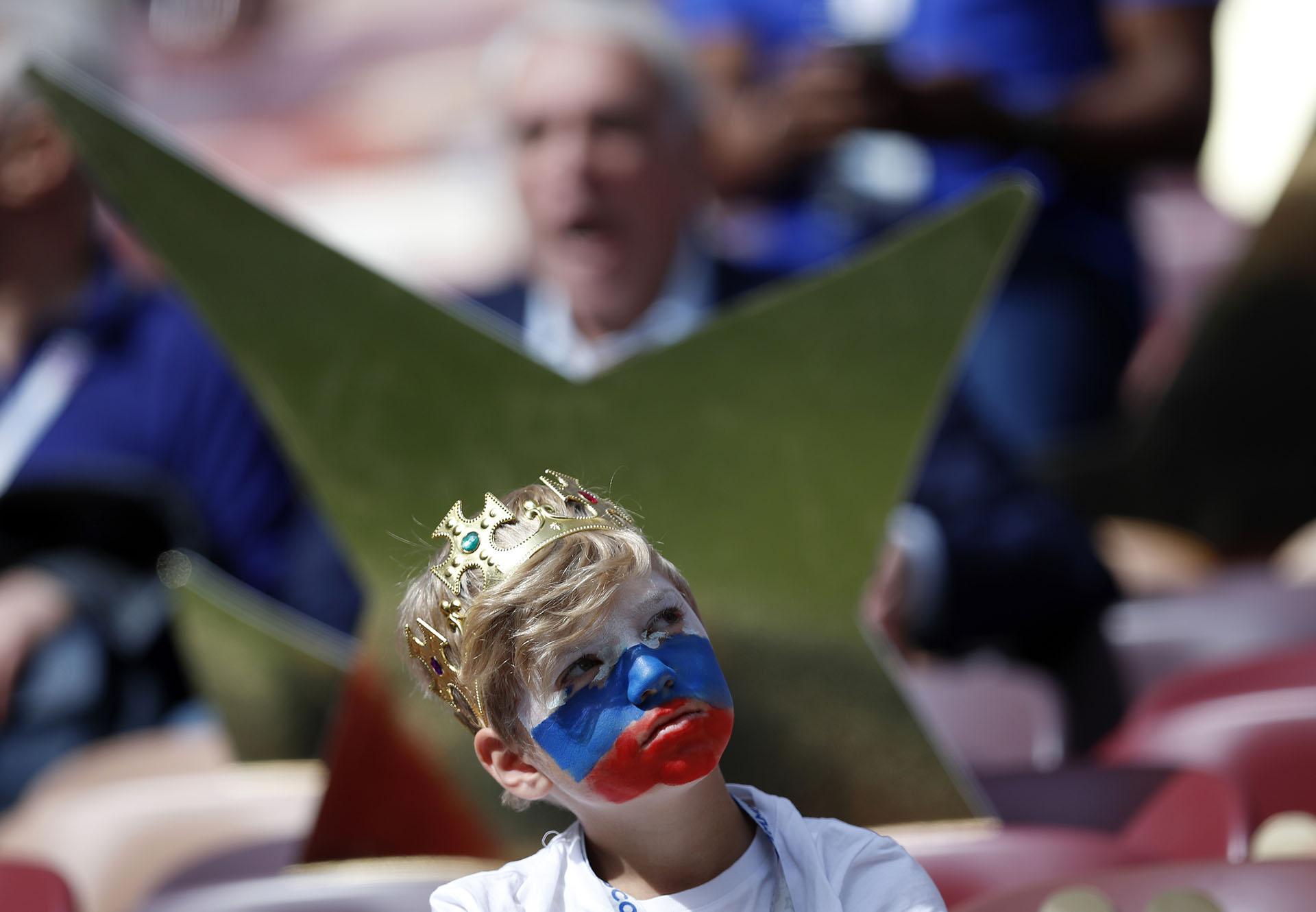Un niño con la corona y el rostro pintado con la bandera rusa esperando el comienzo del primer partido del Mundial (AP Photo/Pavel Golovkin)