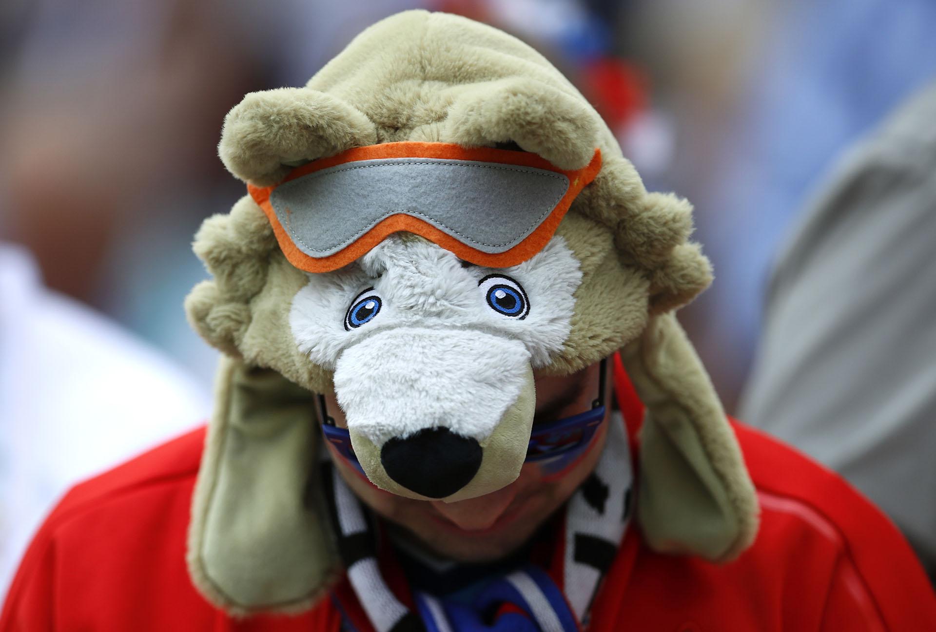 La mascota oficial de Rusia 2018 en la cabeza de un fanático en la antesala de la fiesta de inauguración (AP Photo/Hassan Ammar)