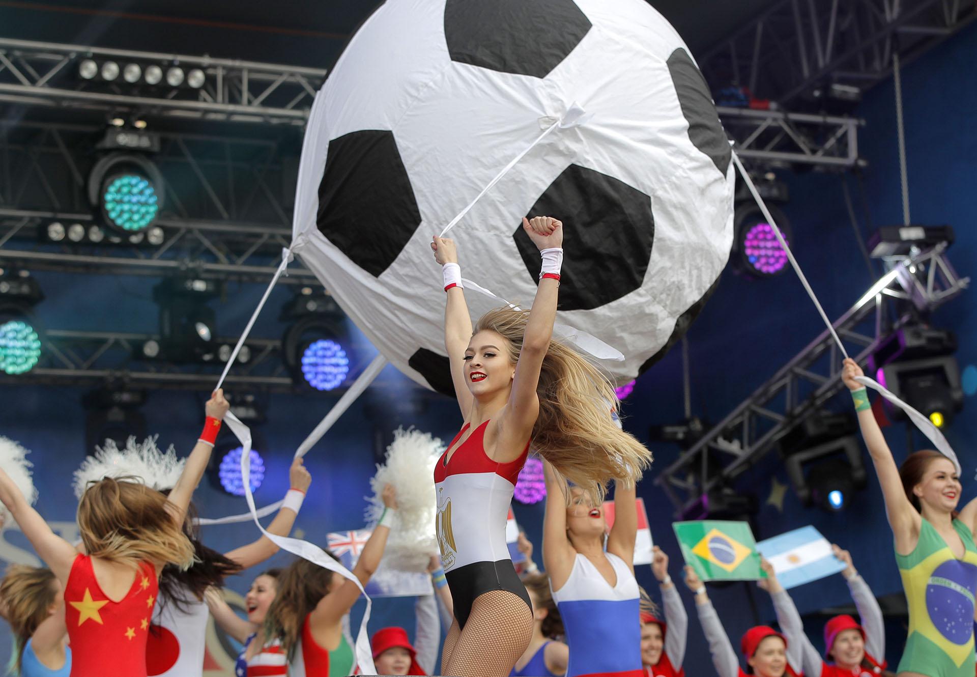 Bailarinasvestidas con trajes de colorescon las banderas de las naciones participantes se presentaron antes del partido inaugural en el fan fest en Ekaterimburgo, Rusia(AP Photo/Vadim Ghirda)