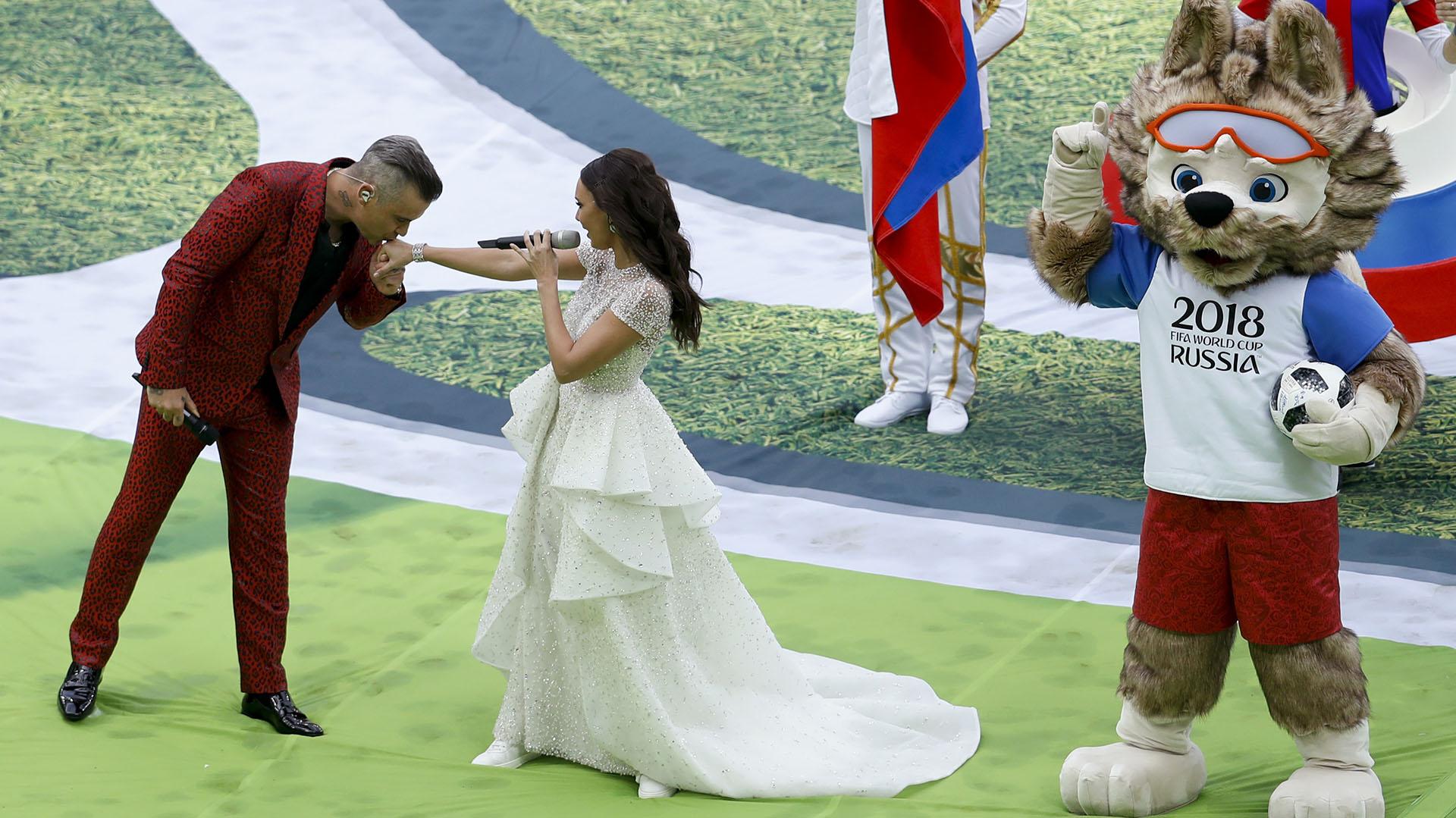 Robbie Williams besa la mano de la soprano Aida Garifullina con la mascota Zavibaka como testigo. Los cantantes interpretaron juntos canciones del artista británico (AP Photo/Victor Caivano)