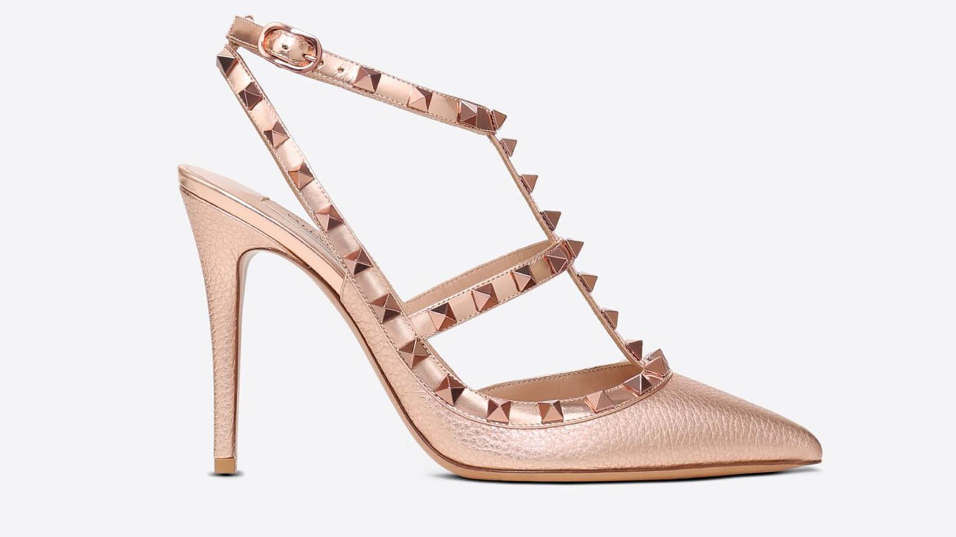 """Por Valentino, el modelo """"Rockstud ankle strap pump"""" en cuero rosado con tachas pirámide y en punta. Este clásico de la firma italiana tiene una gran variedad de colores, detalles y material en el que está confeccionado el zapato"""