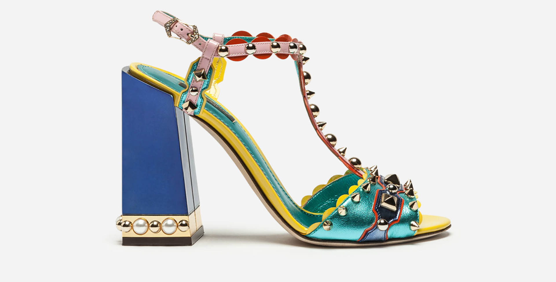 """La sandalia """"Keira"""" con mix de cueros metalizados en verde, amarillo y rosa con taco de madera en forma de trapecio con detalles de dorado y perlas. La pulsera y la tira del zapato están bordadas con tachas sombrerito, en punta y pirámide"""