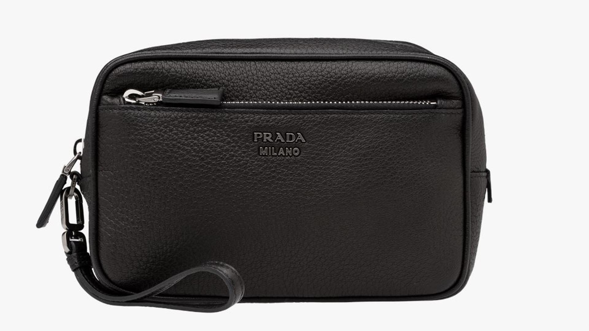 El neceser de cuero negro de Prada con detalle de cierre plateado y correa. La chapa de la firma en el frente (Prada)