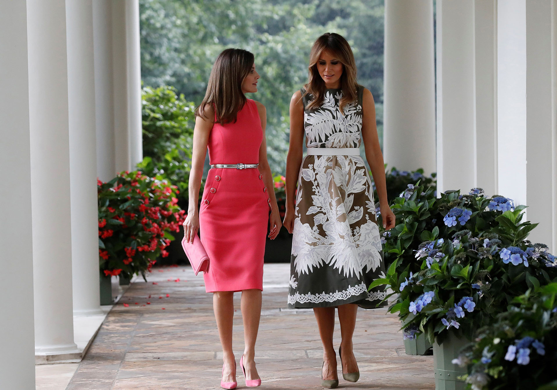 Letizia lució un vestido sin mangas, con un cinturón plateado y botones que marcaban su silueta. Melania eligió uno estampado con dibujos en color blanco, también sin mangas