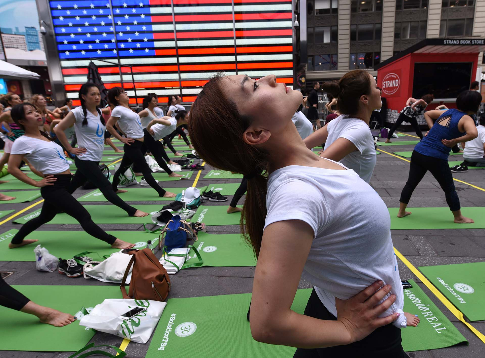 "Thousands of people participate in ""Mind Over Madness Yoga"", an annual all-day outdoor yoga event during the summer solstice in Times Square on June 21, 2018 in New York. / AFP PHOTO / TIMOTHY A. CLARY"