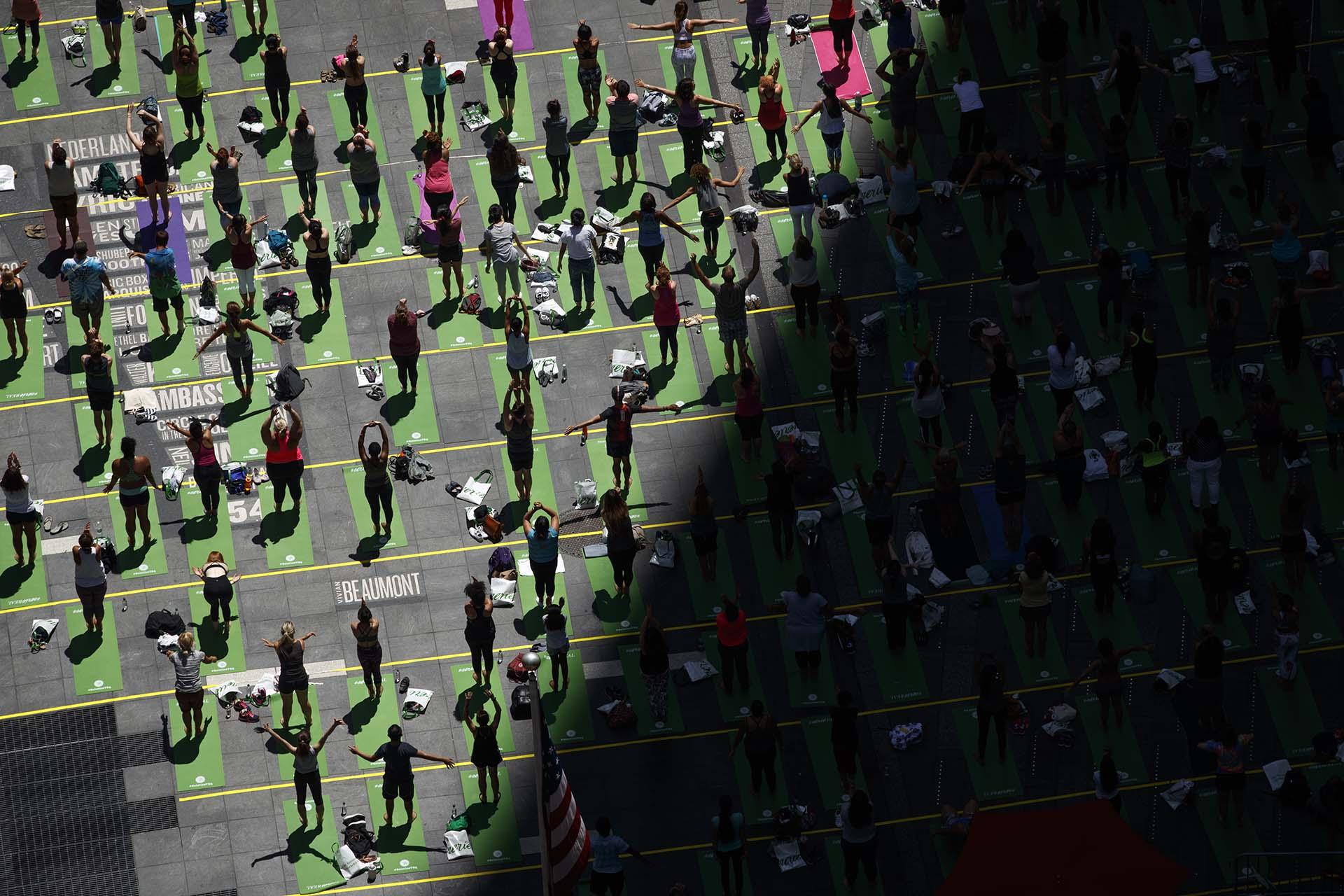 Fanáticos del yoga participan de una clase masiva al aire libre en Time Square (Drew Angerer/Getty Images/AFP)