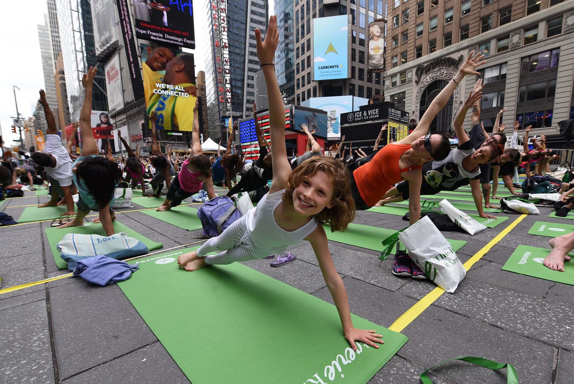 Kate Steinberg, de 9 años y oriunda de Montreal, junto a miles de personas celebrando el Día Mundial del Yoga (AFP PHOTO / TIMOTHY A. CLARY)