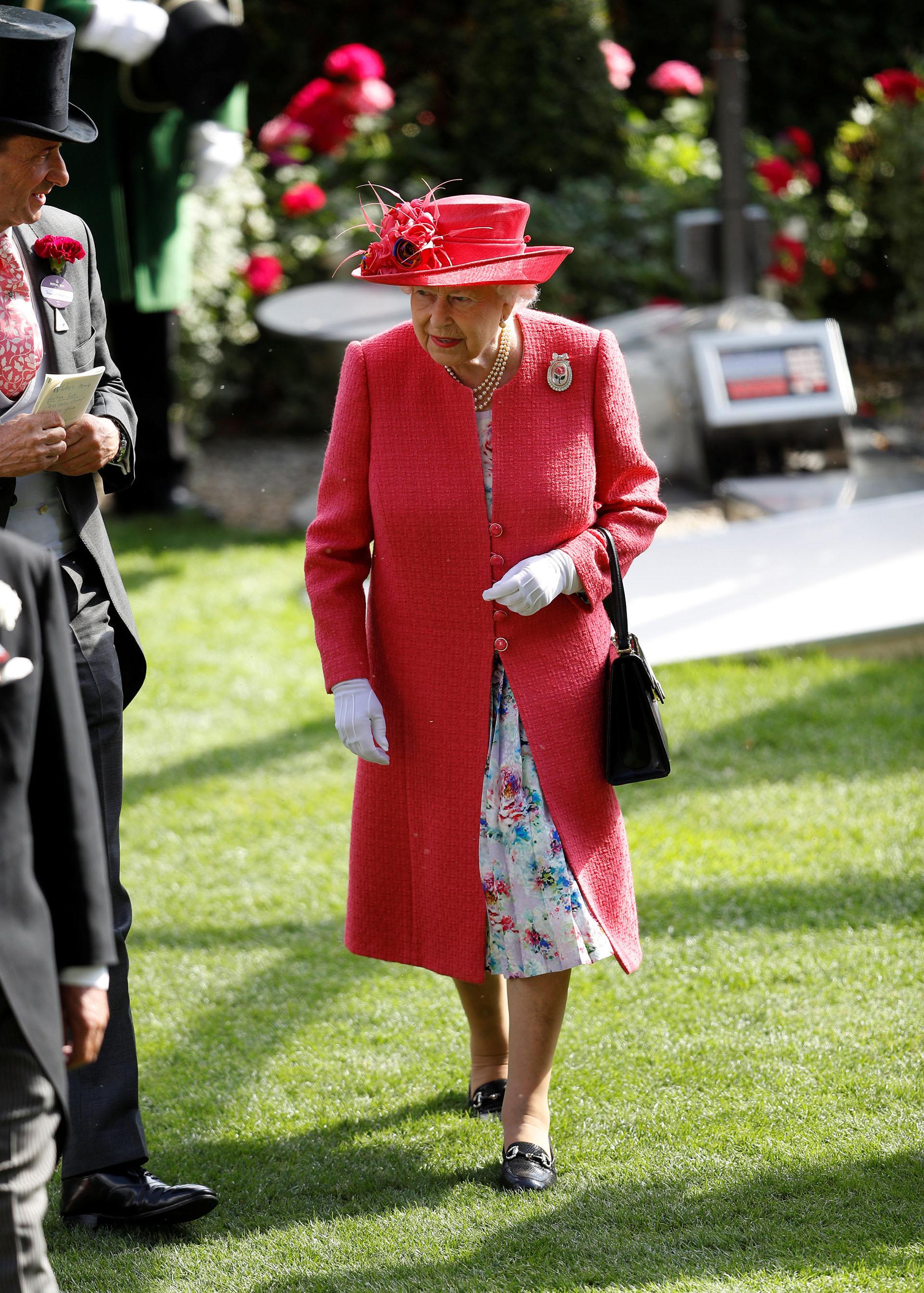 La reina lució un tapado rosa que hacía juego con su sombrero y dejaba ver un vestido con estampa floral