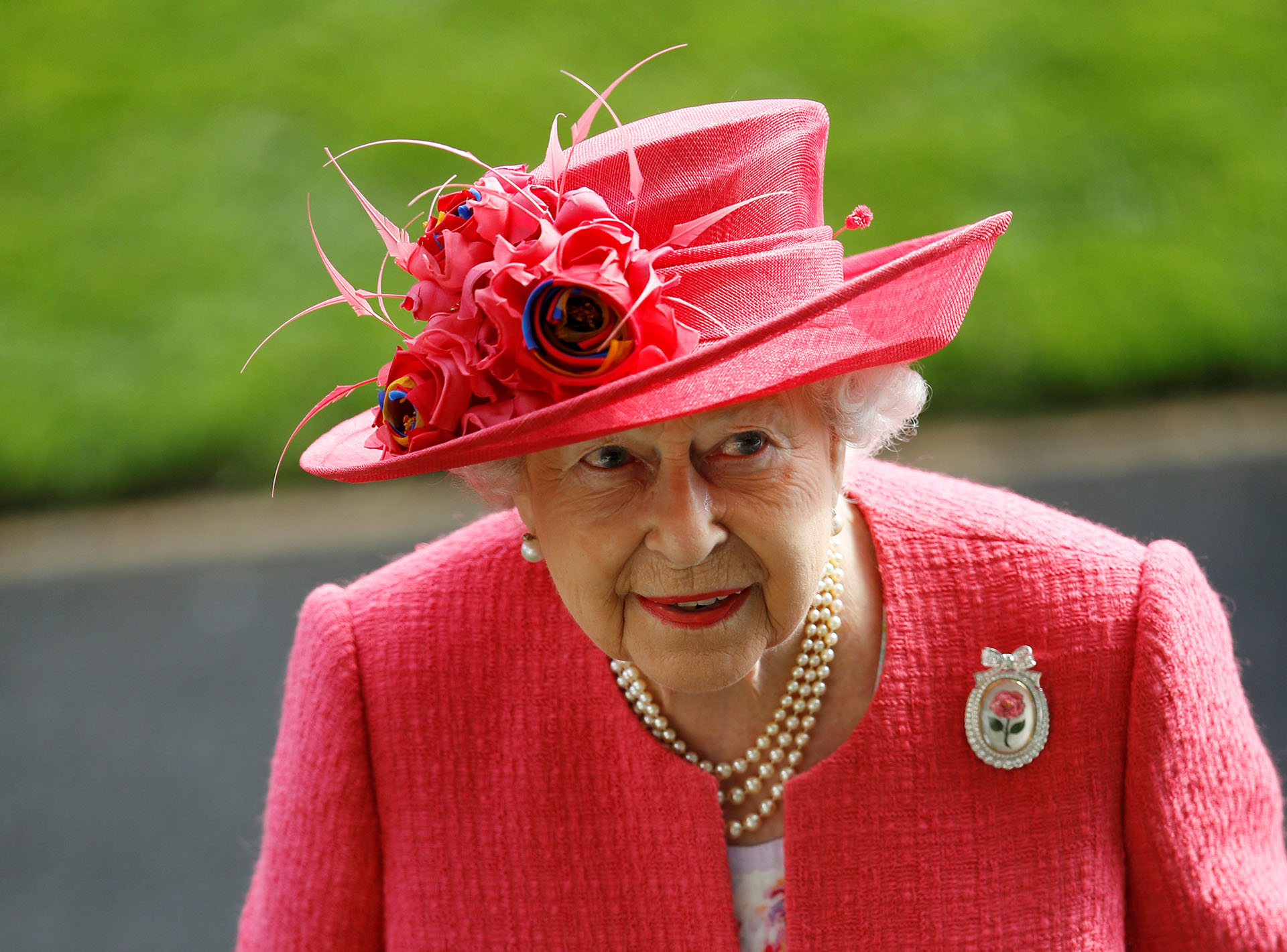 El detalle del broche en el tapado, con una flor haciendo juego con su ropa, y su infaltable collar de perlas de tres vueltas, en conjunto con sus aros