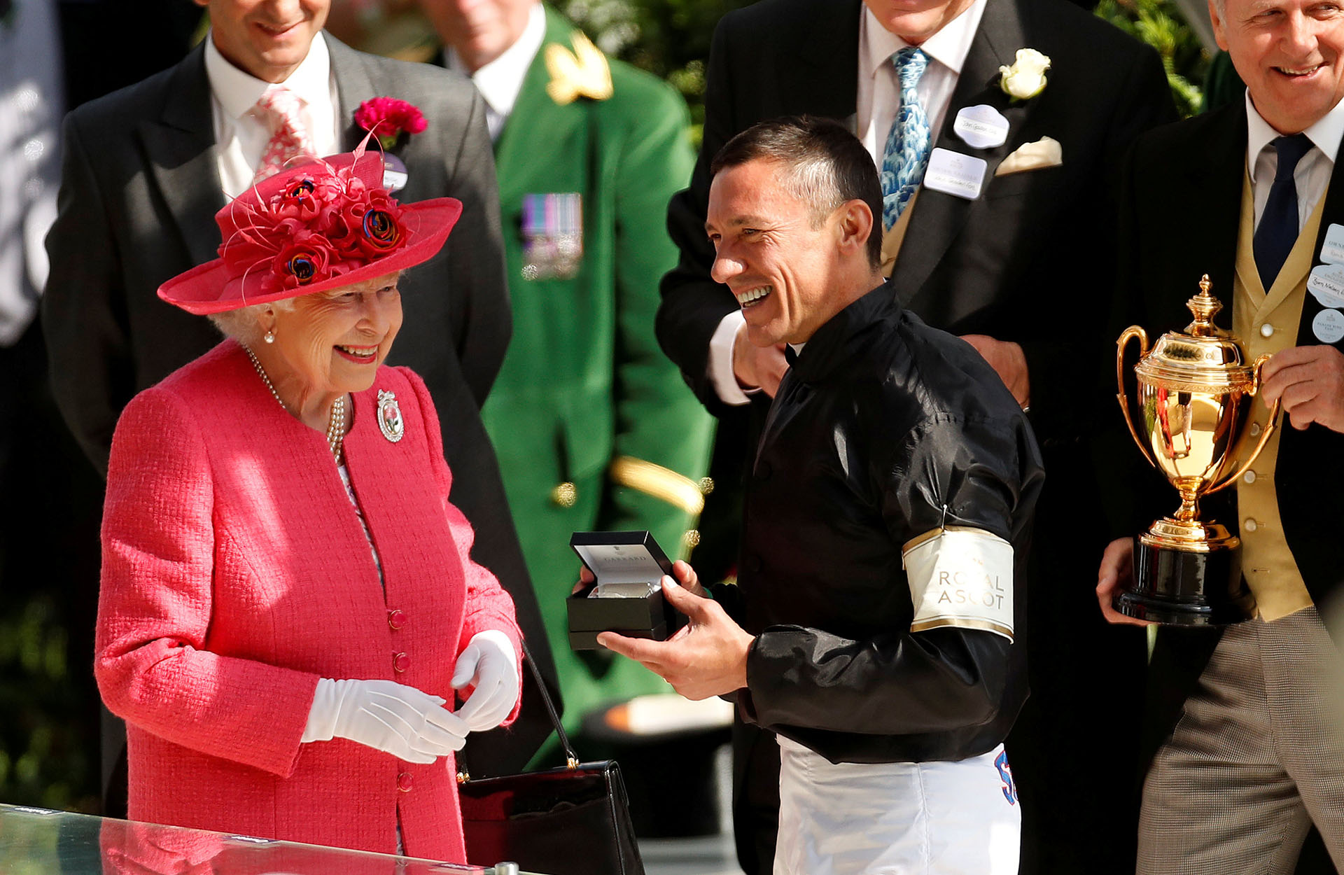 La monarca sonríe junto a uno de los ganadores, Frankie Dettori