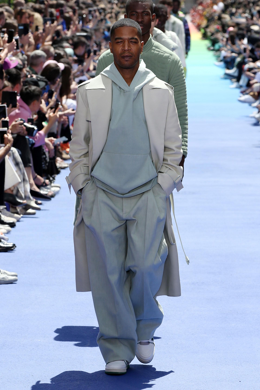 Una combinación entre la sastrería y el sportwear. Pantalones de vestir, hoodie, trench y zapatillas deportivas