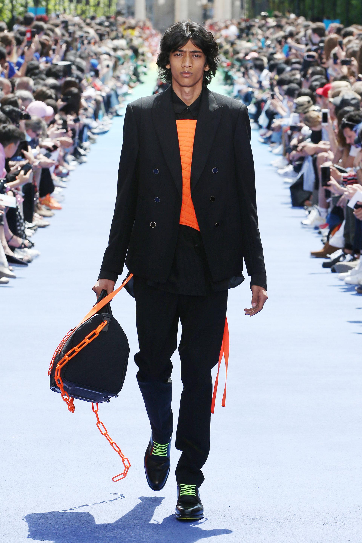 Naranja flúo y negro, una combinación de colores explosiva. Un pantalón de vestir chupín y blazer. Debajo, camisa negra con estampado naranja. Para acompañar el look, el bolso Keepall combinado con naranja flúo. ¿El detalle? Los zapatos negros con cordones verde flúo