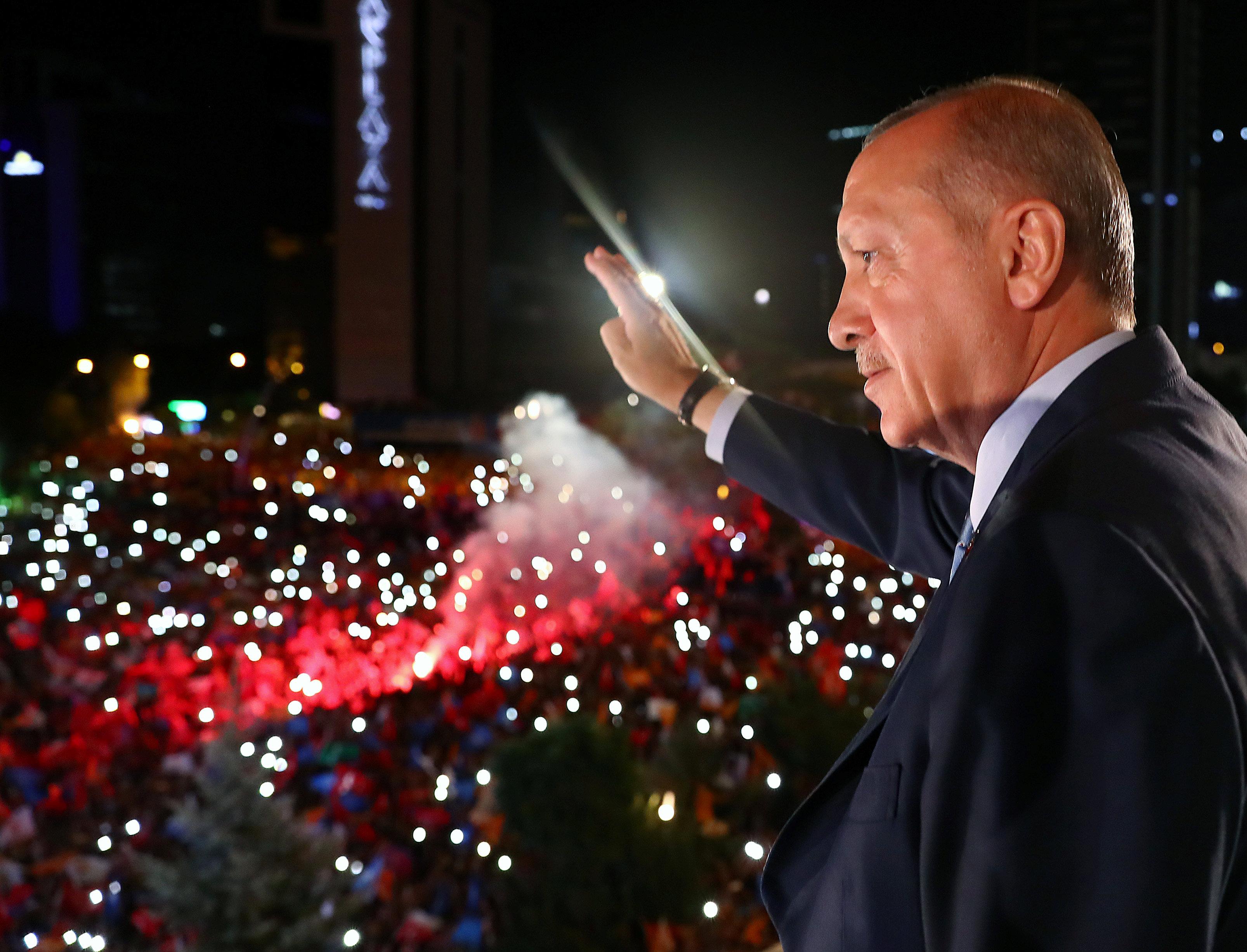 El presidente turco Tayyip Erdogan saluda a sus seguidores desde el balcón de la sede de su partido gobernante, el AK, en Ankara, Turquía, a principios del 25 de junio de 2018. (Reuters)