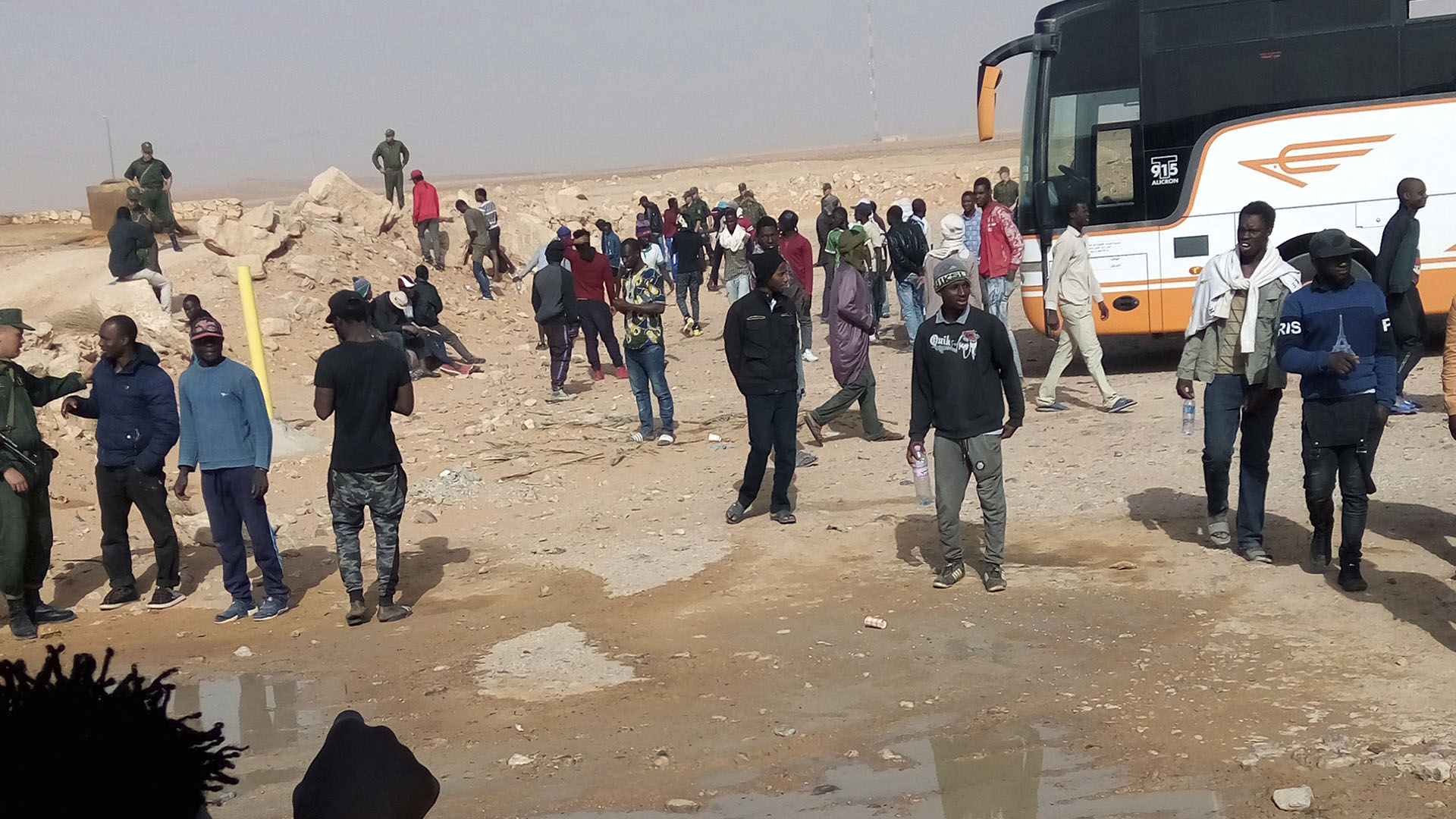 Un grupo de migrantes espera la deportación mientras es vigilado por soldados argelinos (AP)