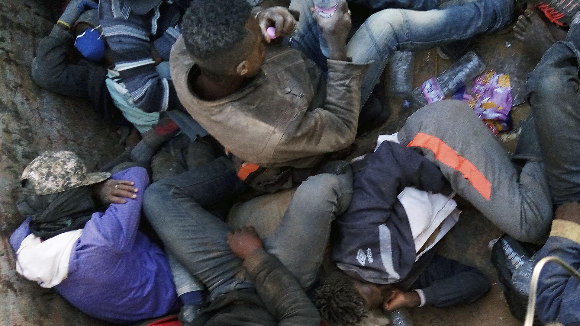 Migrantes descansan en un camión en el que militares argelinos los trasladan para abandonarlo en el desierto y obligarlos a caminar amenazados con rifles AK-47 (AP)