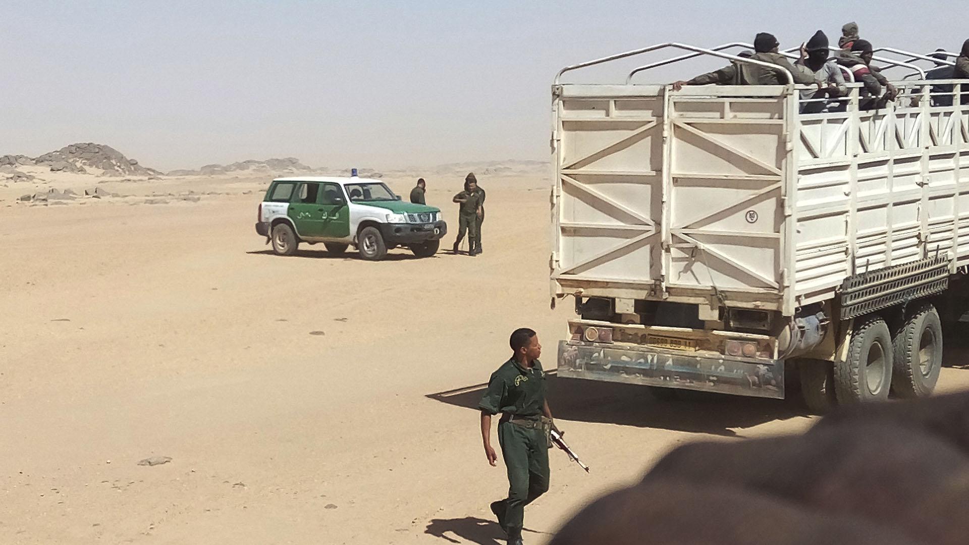 Soldados argelinos armados con rifles de fabricación rusa colocan a los migrantes en camiones y los abandonan en la frontera con Níger, en medio del desierto(AP)