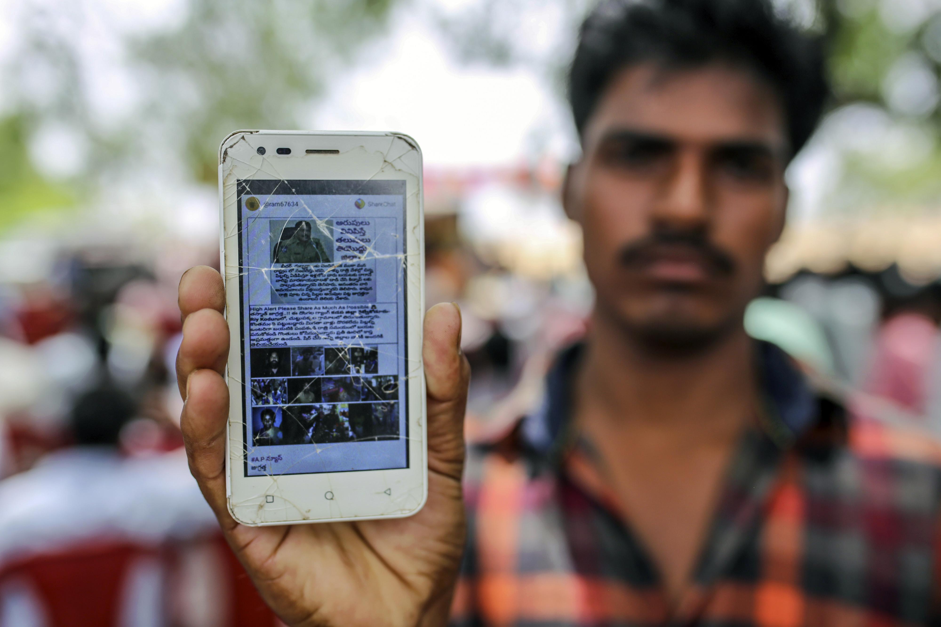 Un hombre muestra la pantalla de su teléfono celular con un mensaje falso difundido a través de WhatsApp (Bloomberg / Dhiraj Singh)
