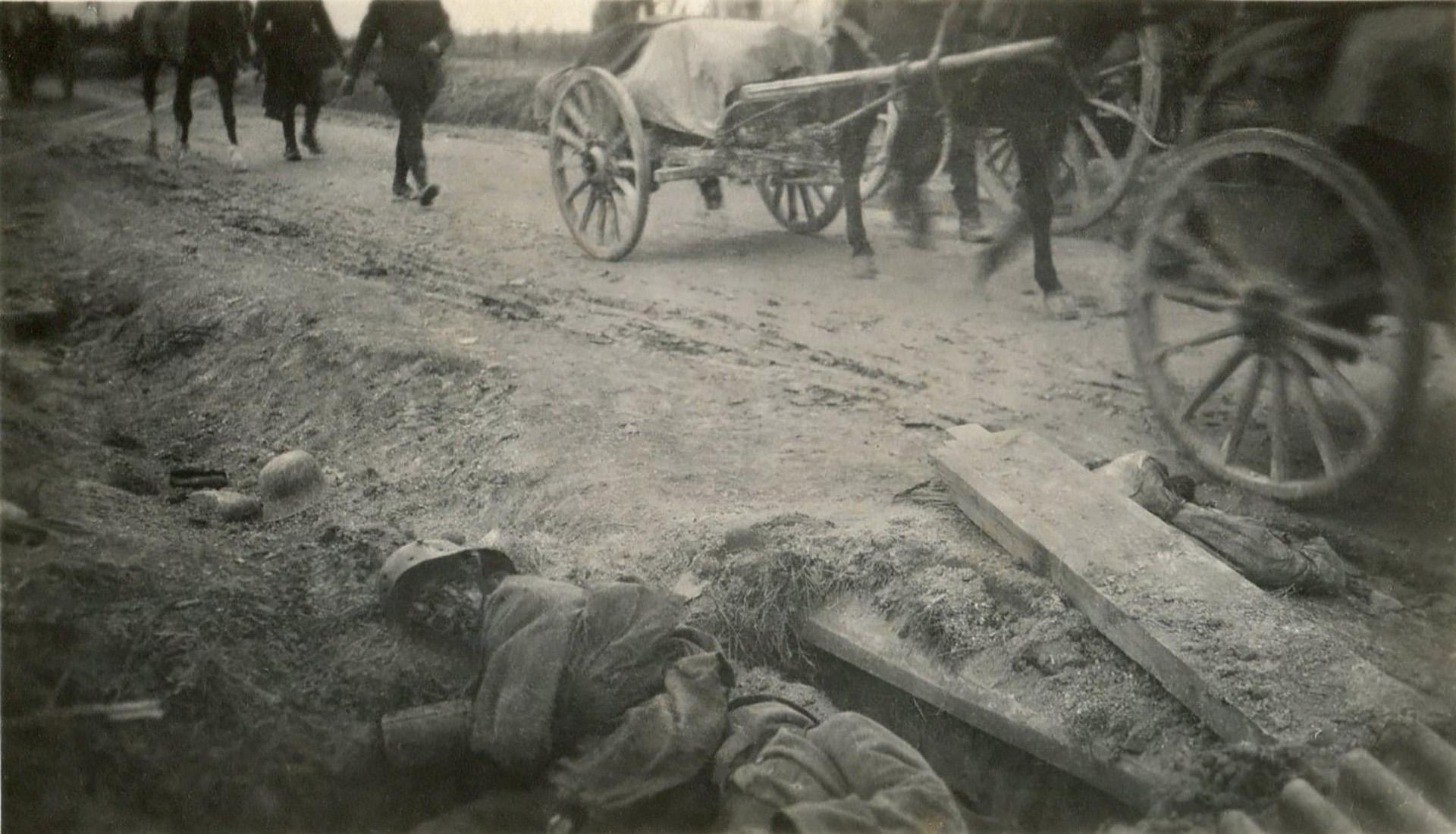 Este soldado alemán yace muerto en una zanja mientras la columna aliada de carros y caballos avanza