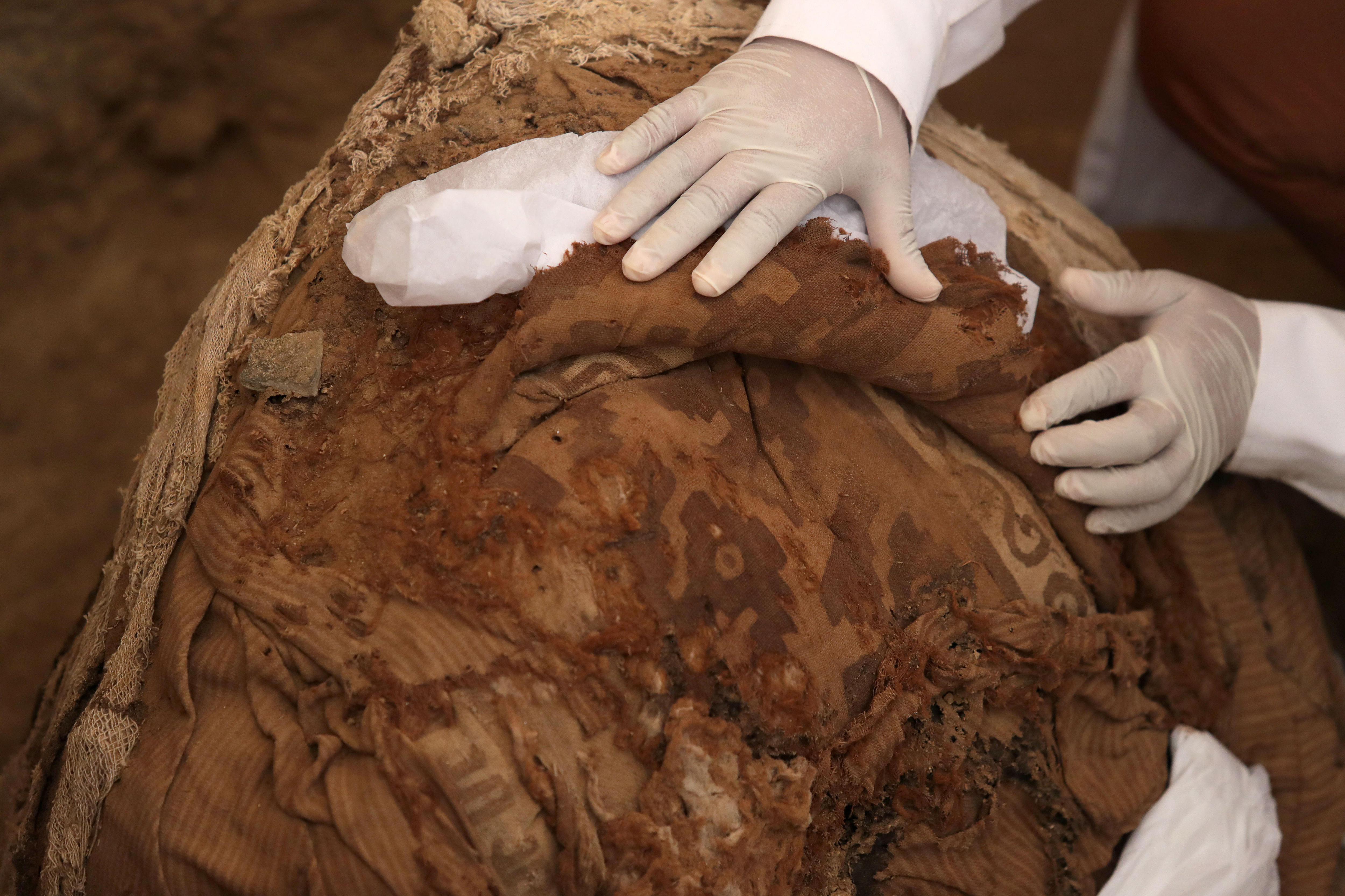 Un arqueólogo trabaja con un fardo funerario(EFE)