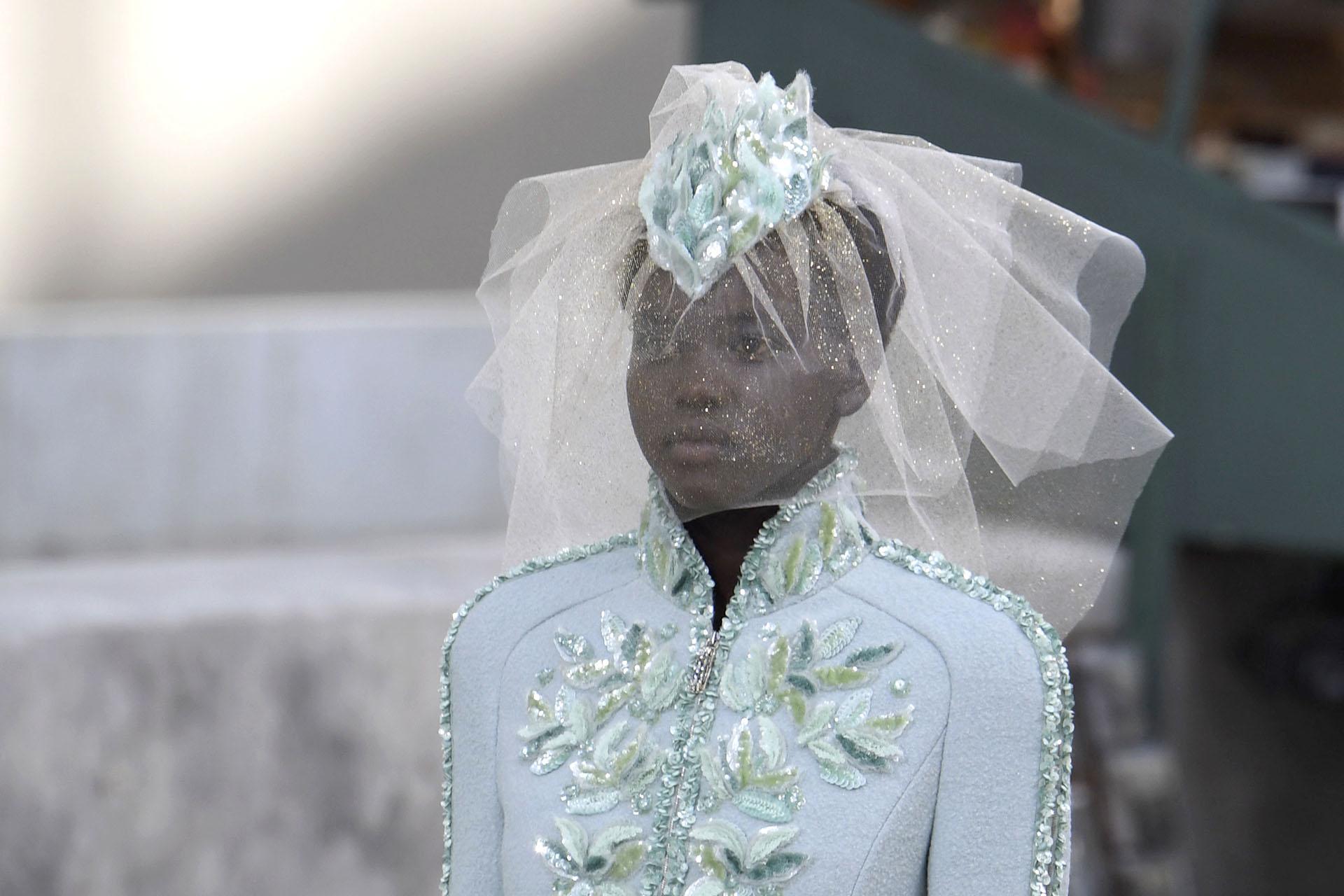 Adut Akech, la modelo sudafricana-australiana, estuvo presente en el desfile de Chanel y lució un diseño de chaqueta de paño con detalles únicos de bordados en tonos celeste hielo y verdes. Los tocados de la colección presentada por Karl Lagerfeld llamaron la atención por la originalidad y la perfecta combinación con los equipos