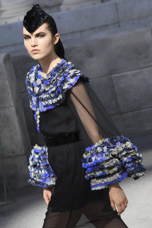 Transparencias, sedas, gasas, tweed y mix de géneros no faltaron en la pasarela de Chanel. Un diseño que combino texturas y géneros nobles coronado con un tocado pequeño de plumas.