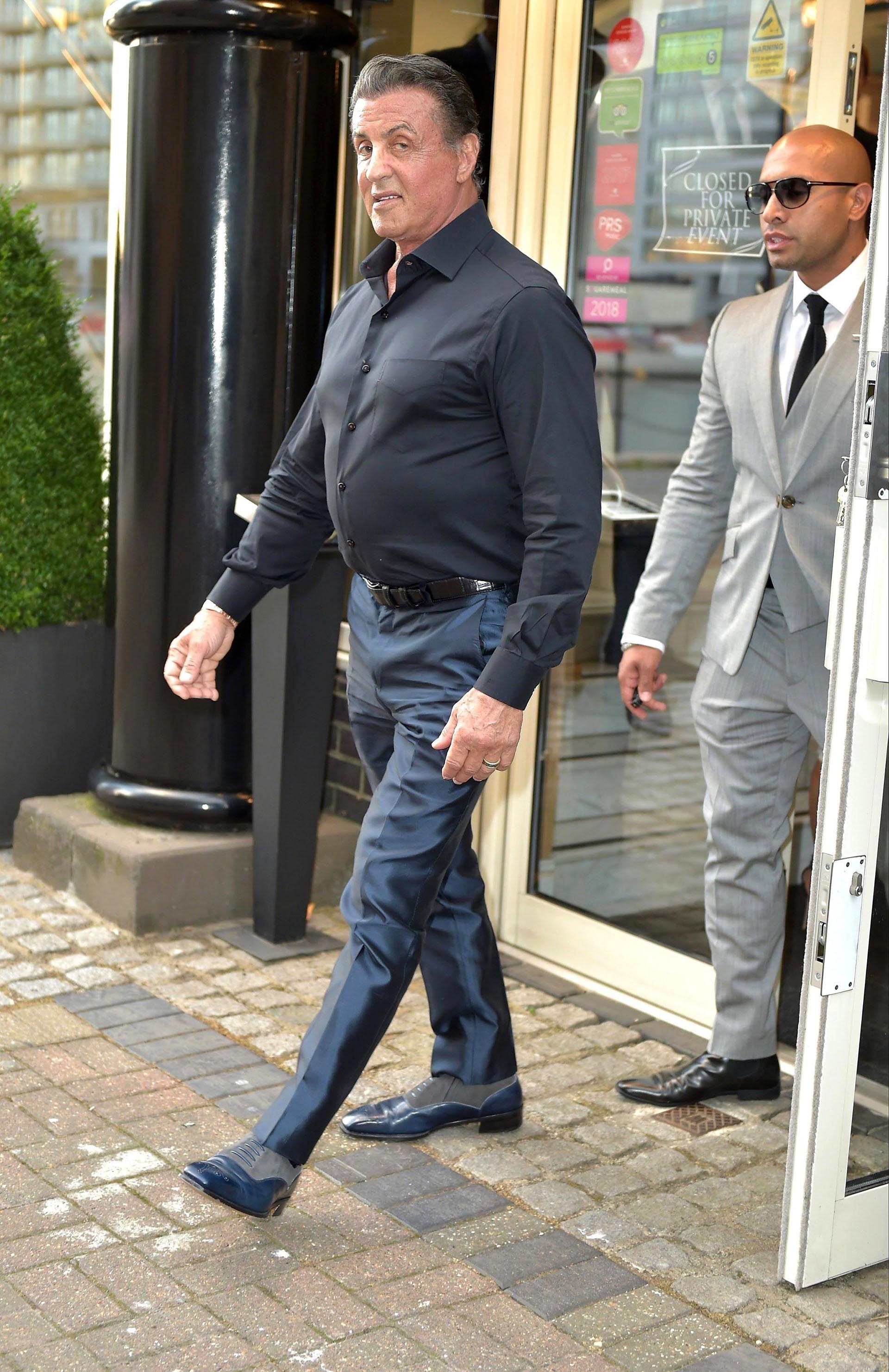 Vestido con un traje azul, zapatos combinados con gris y camisa negra, Stallone conserva su elegancia característica (Grosby Group)