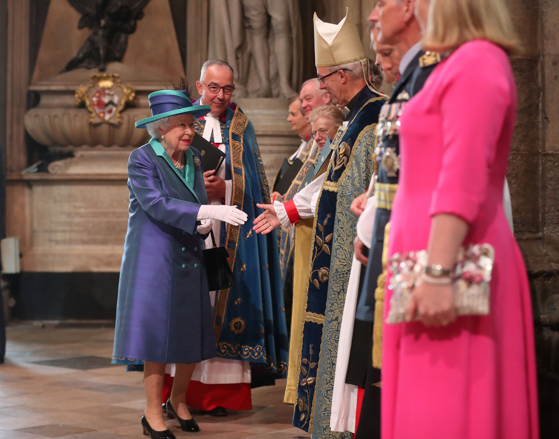 La monarca eligió una delicada combinación de colores: un tapado violeta tornasol con detalles turquesa, incluso en su sombrero