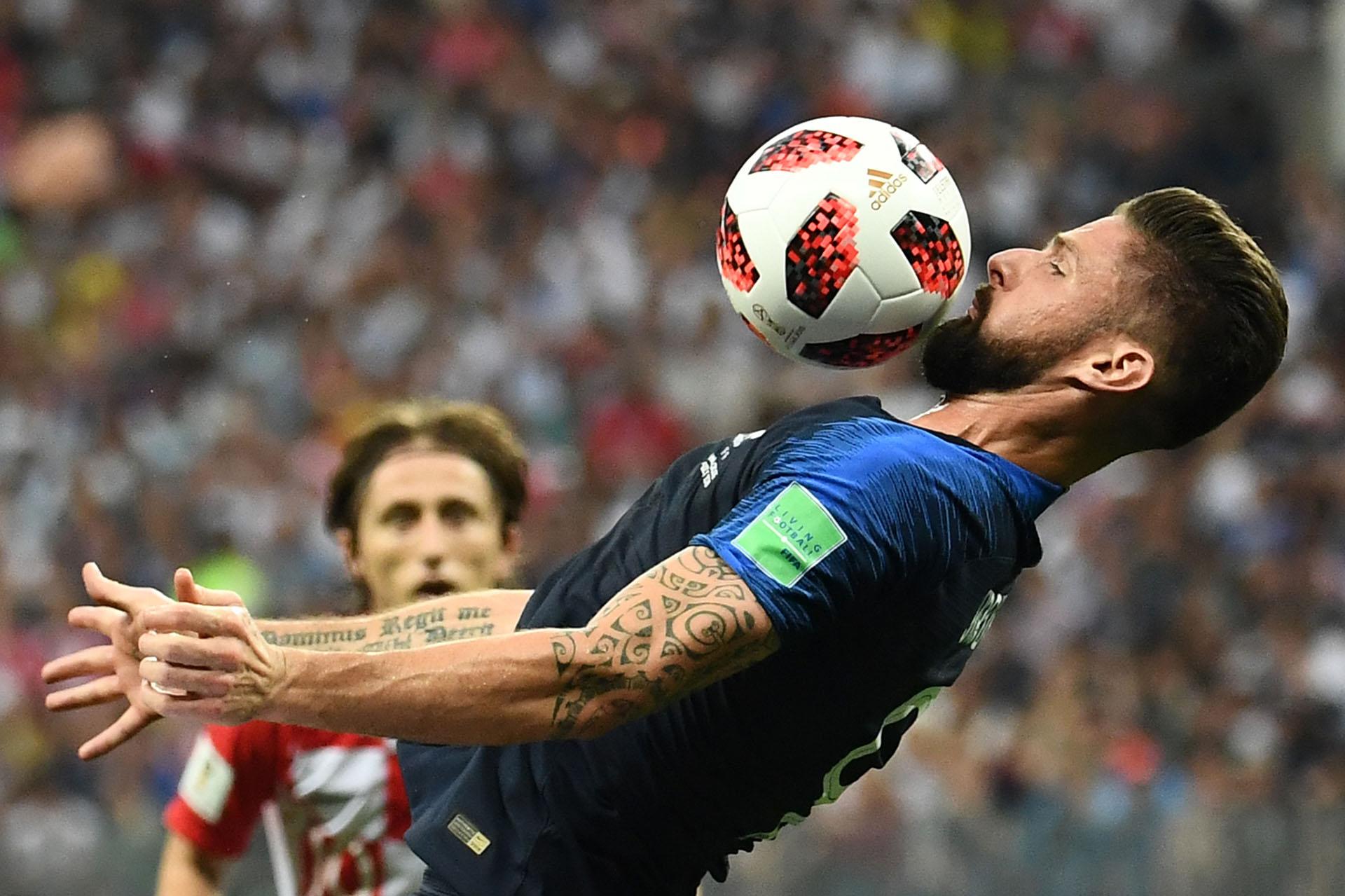 El francés Olivier Giroud mata el balón con su pecho; detrás lo mira el croata Luka Modric