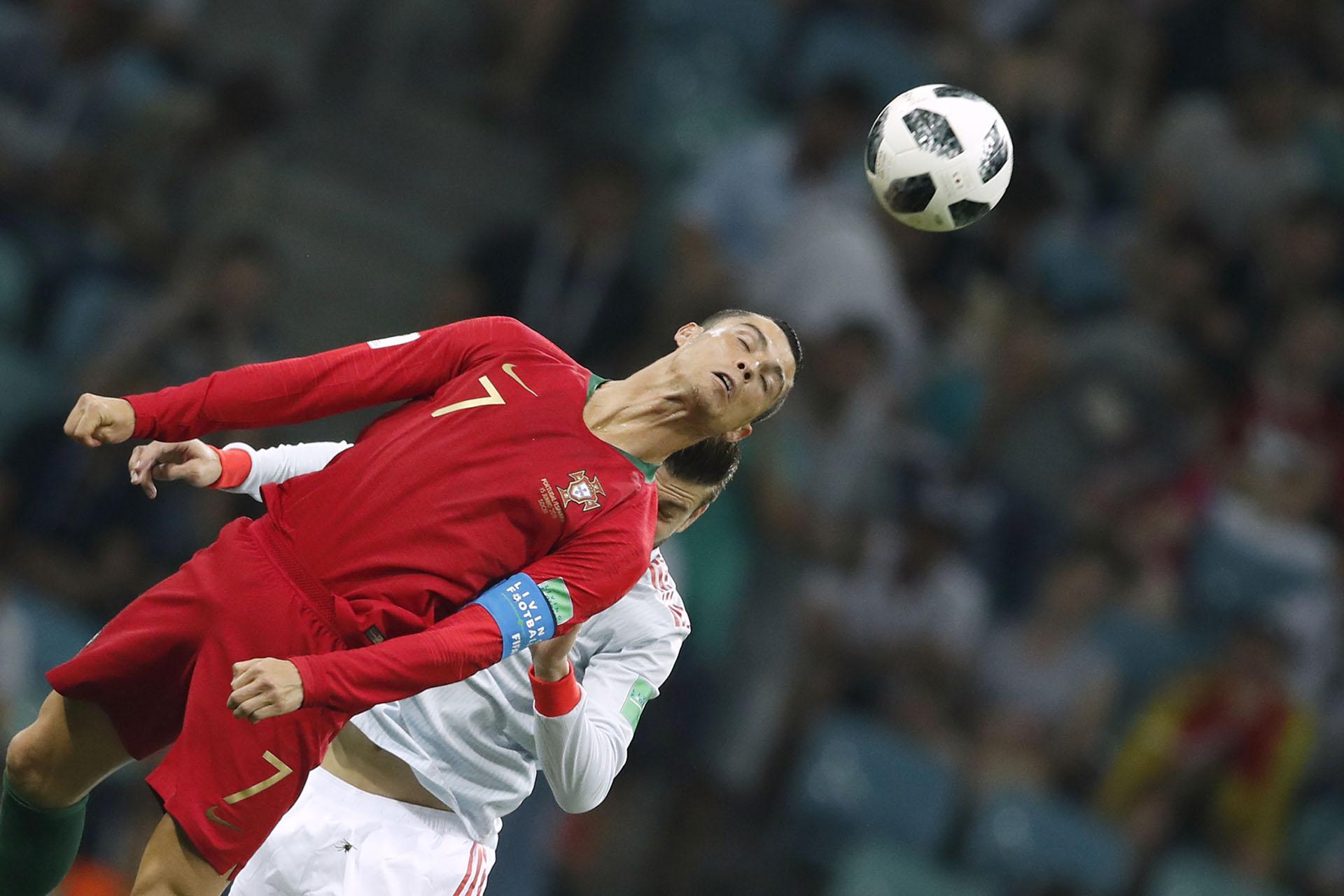 El portugués Cristiano Ronaldo anticipa de cabeza al español Gerard Piqué durante el partidazo del debut