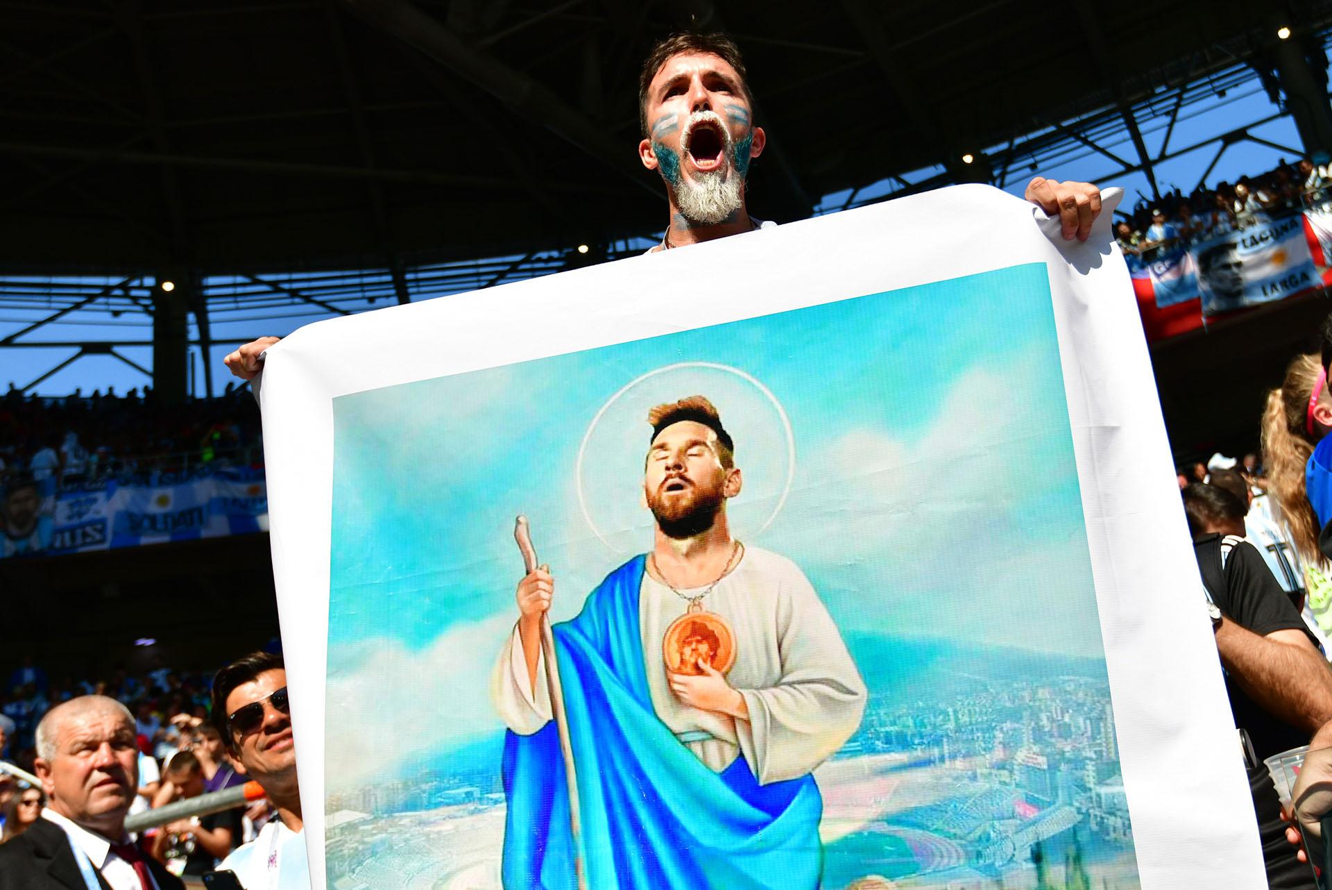 La estampita gigante de Lionel Messi es mostrada por un fanático argentino