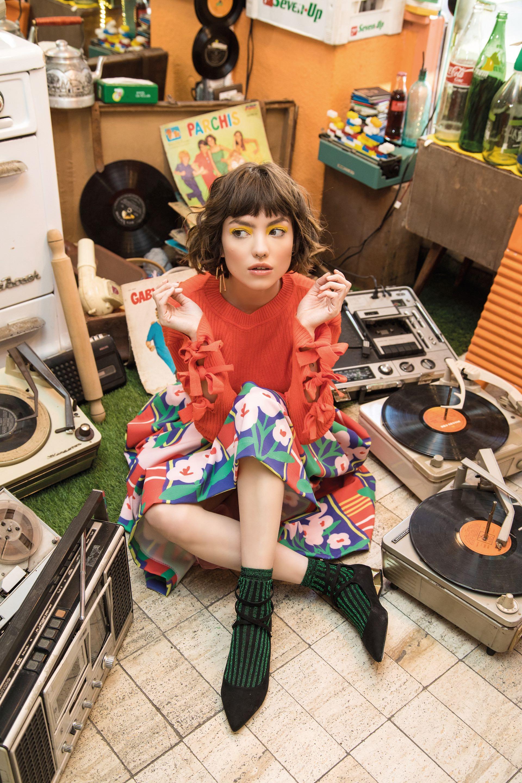 Suéter con lazos en las mangas y medias de lúrex ($ 1.790 y $ 199, Las Pepas), falda estampada (Mila Kartei) y zapatos de gamuza con taco dorado ($ 2.400, Aldo en Grimoldi). (Foto: Fernando Venegas/ Para Ti)
