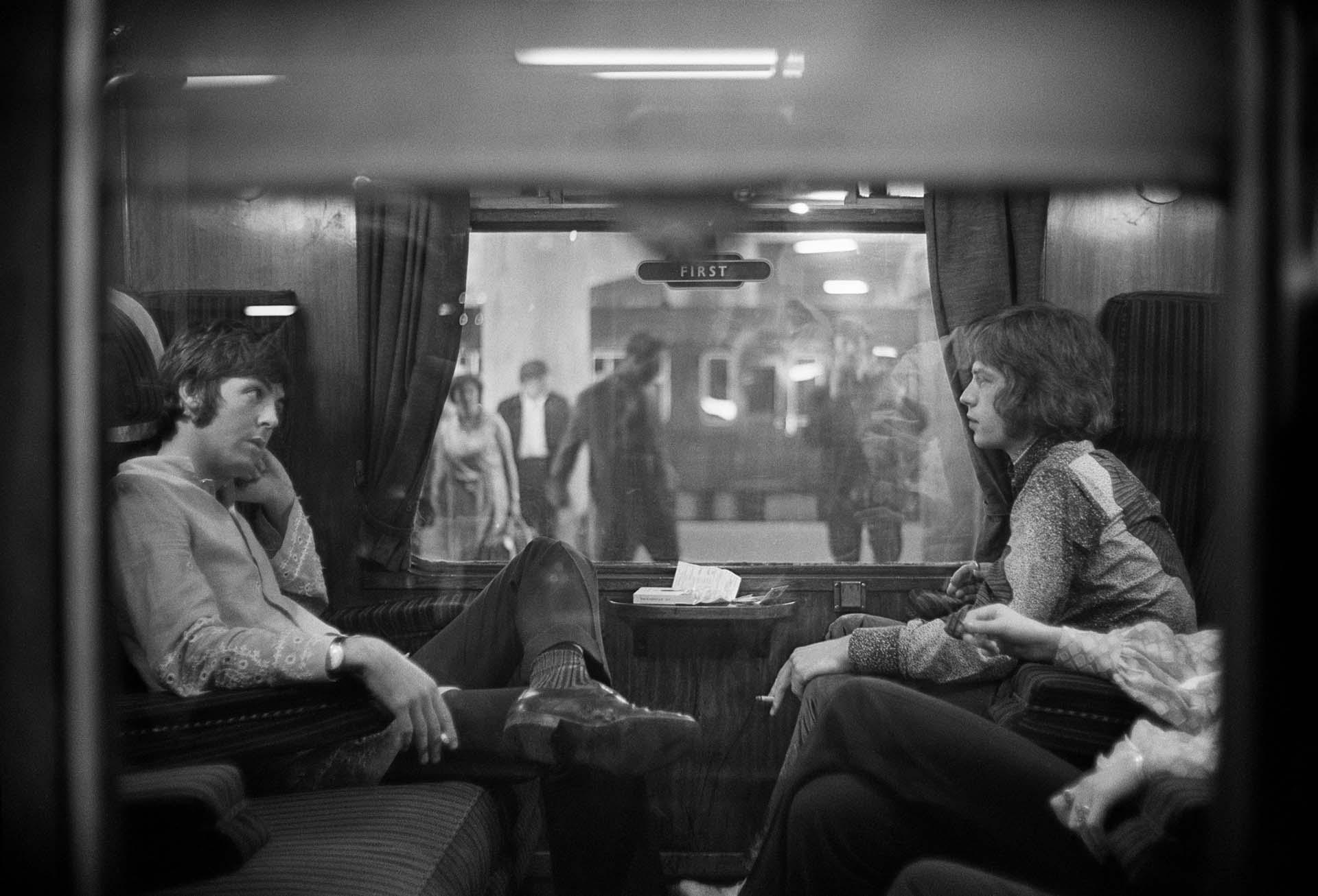 25 de agosto de 1967: Paul McCartney de los Beatles y Mick Jagger de los Rolling Stones se sientan uno frente al otro en un tren en la estación de Euston, esperando la partida a Bangor