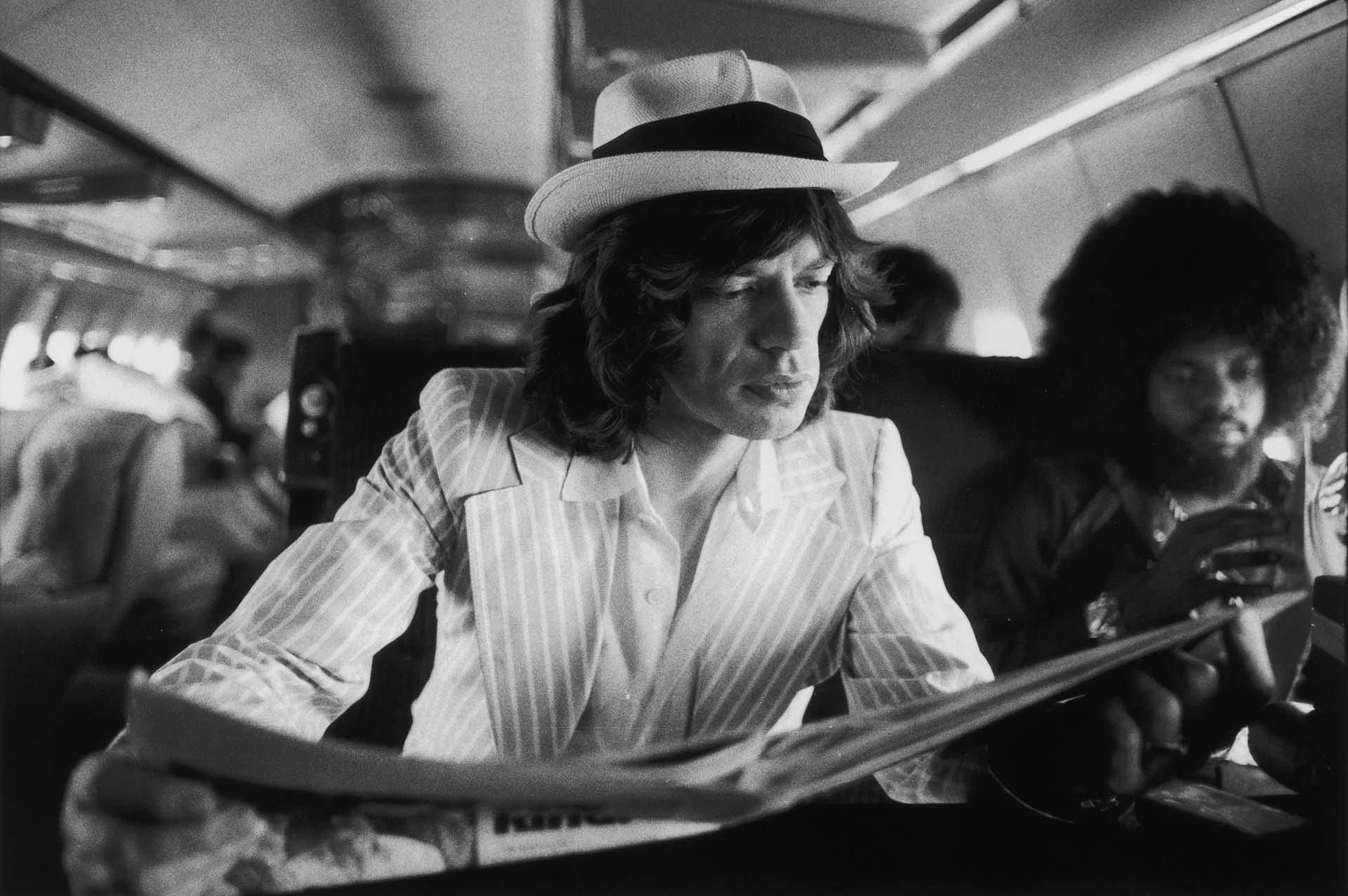 Mick Jagger lee los periódicosmientras viaja entre conciertos en el jet privado de los Rolling Stones durante su Tour of the Americas de 1975. También a bordo está el tecladista estadounidense Billy Preston (derecha).