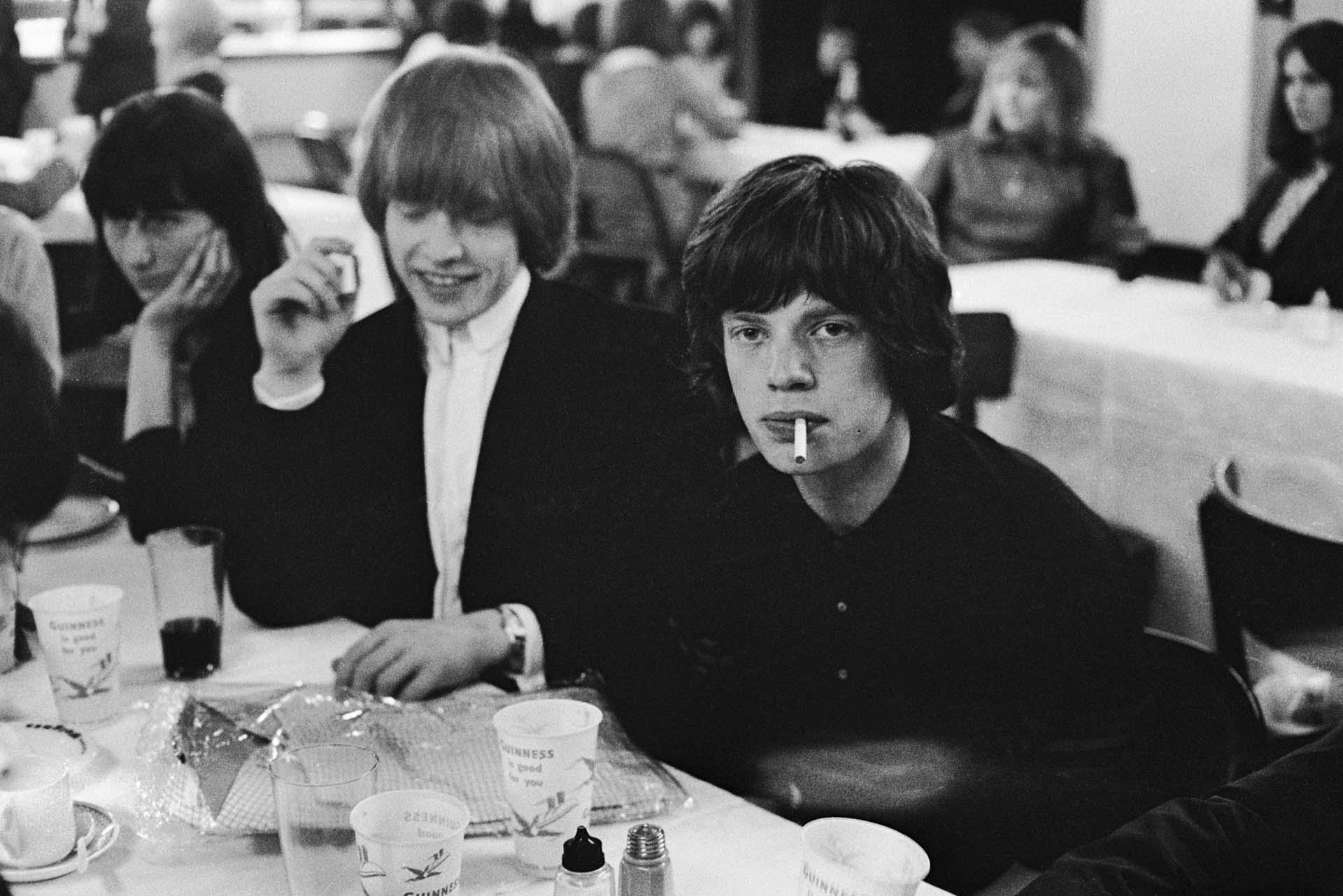 Brian Jones (1942 – 1969) y Mick Jagger de los Rolling Stones toman refrigerios en una cantina, alrededor de 1965.